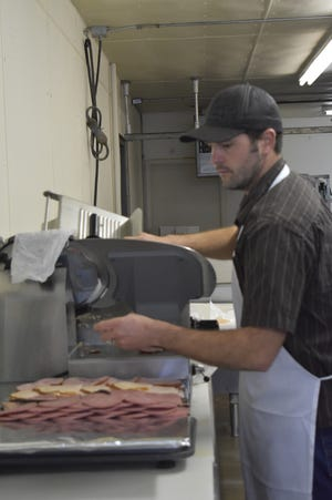 Ben Handl slices meat for a meat and cheese tray.