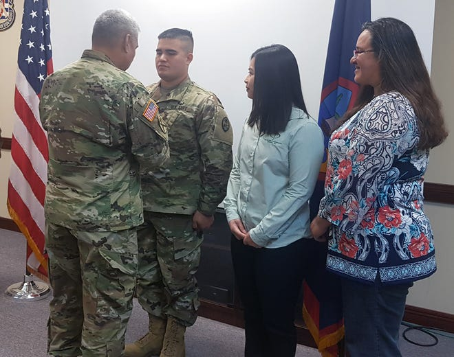 Maj. Gen. Roderick Leon Guerrero, adjutant general of the Guam National Guard, gives Sgt. Jerome Carriaga the Guam Cross of Valor, for helping save the life of a driver involved in a Feb. 21 accident, during a ceremony held at the Guam National Guard Readiness Center on Dec. 3, 2018. With Carriaga are his wife Camarin Carriaga and mother Janice Shimizu.