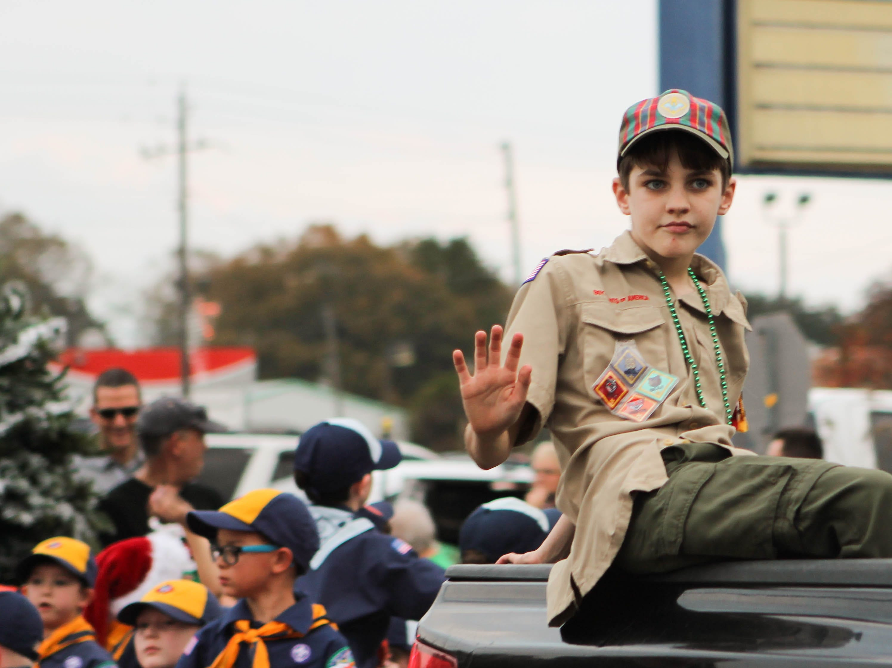 A Boy Scout waves to children in the crowd of the Petal Christmas Parade on Saturday, December 1, 2018.