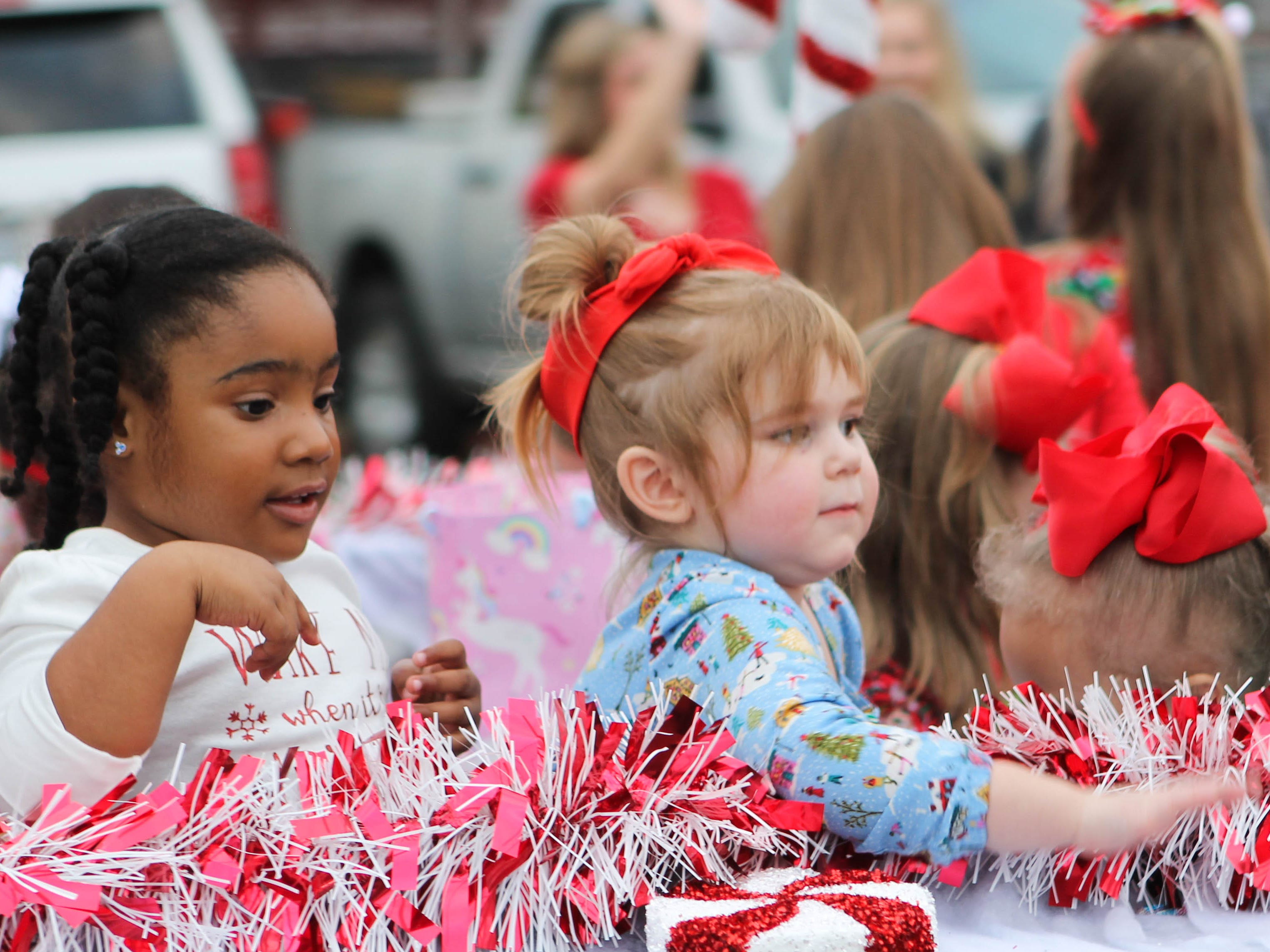 Young girls throw candy at parade spectators on Saturday, December 1, 2018.