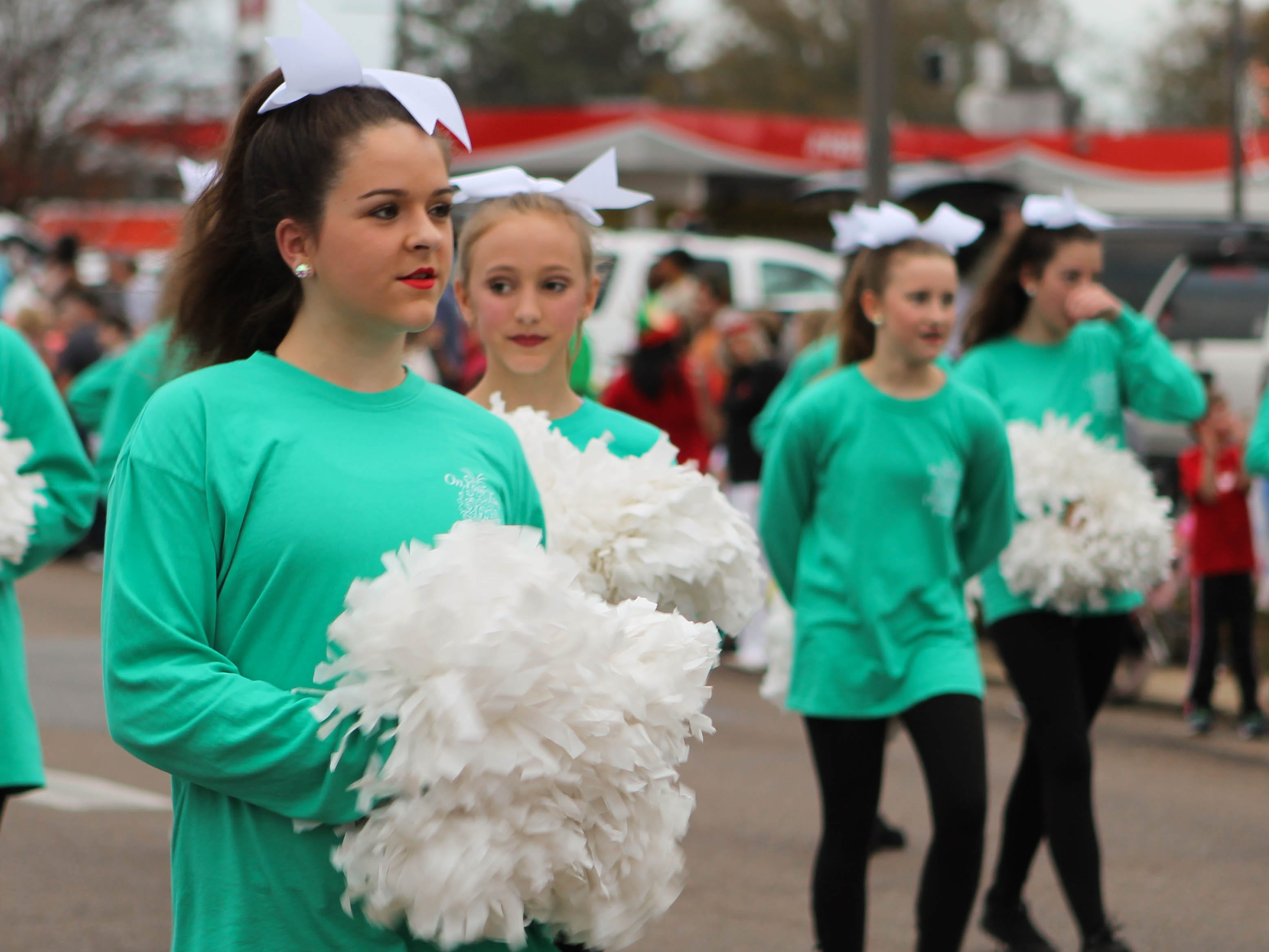 Dance Company members sport pompoms as they walk in the Petal Christmas Parade on Saturday, December 1, 2018.