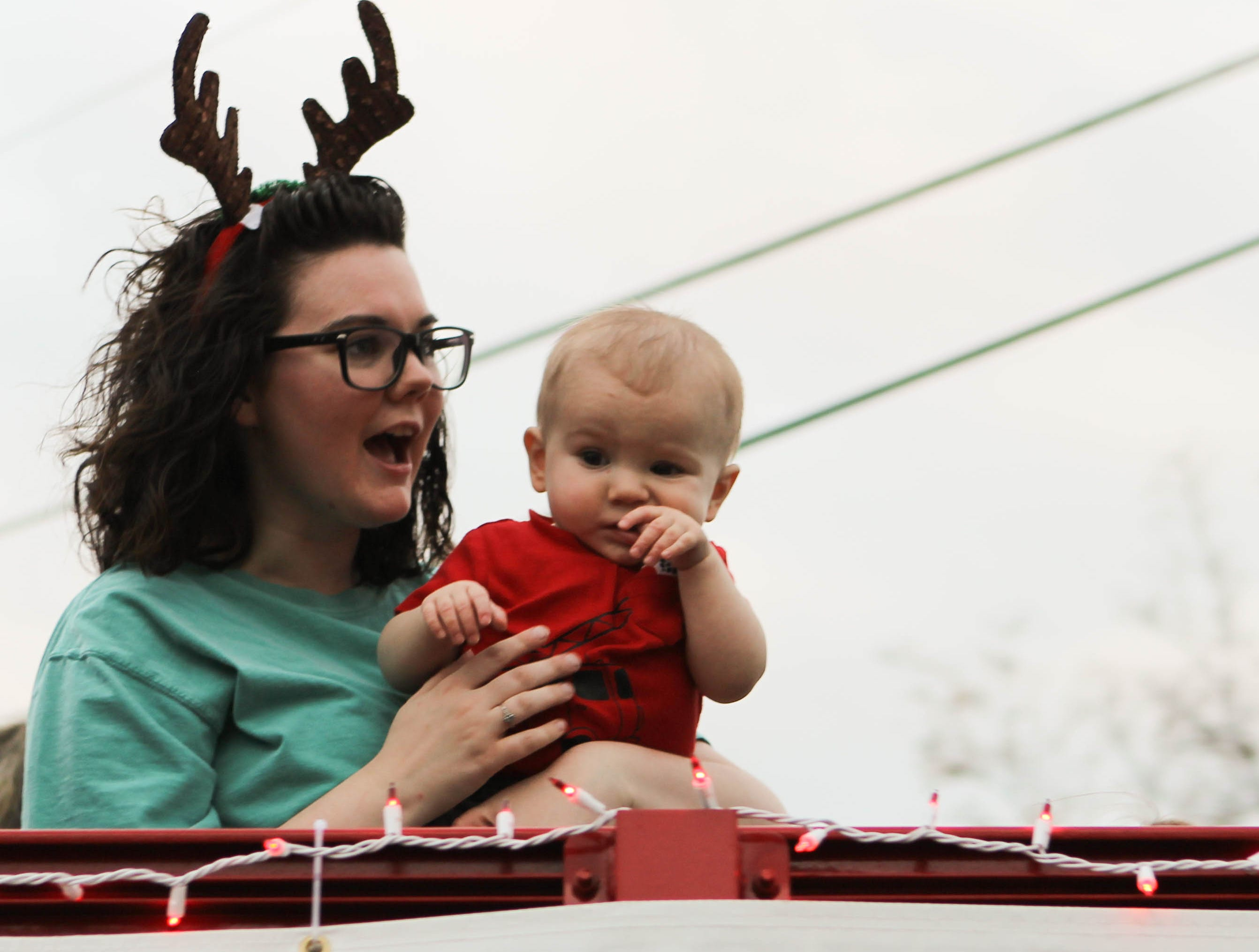 Sporting reindeer antlers, a parade participant holds a baby during the Christmas parade in Petal on Saturday, December 1, 2018.