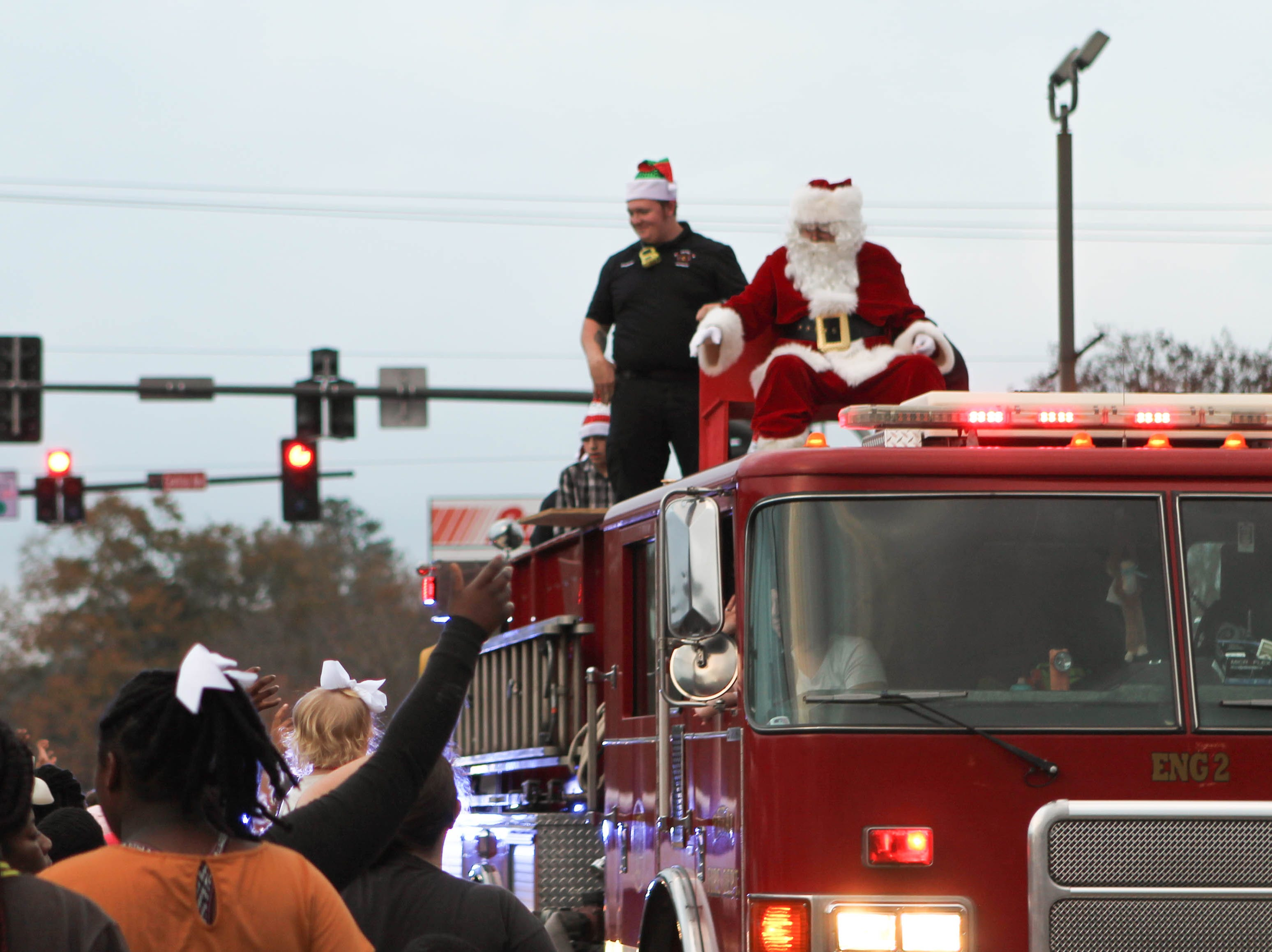 Sitting on top of a fire truck, Santa Claus waves to parade spectators, indicating the end of the Petal Christmas Parade on Saturday, December 1, 2018.
