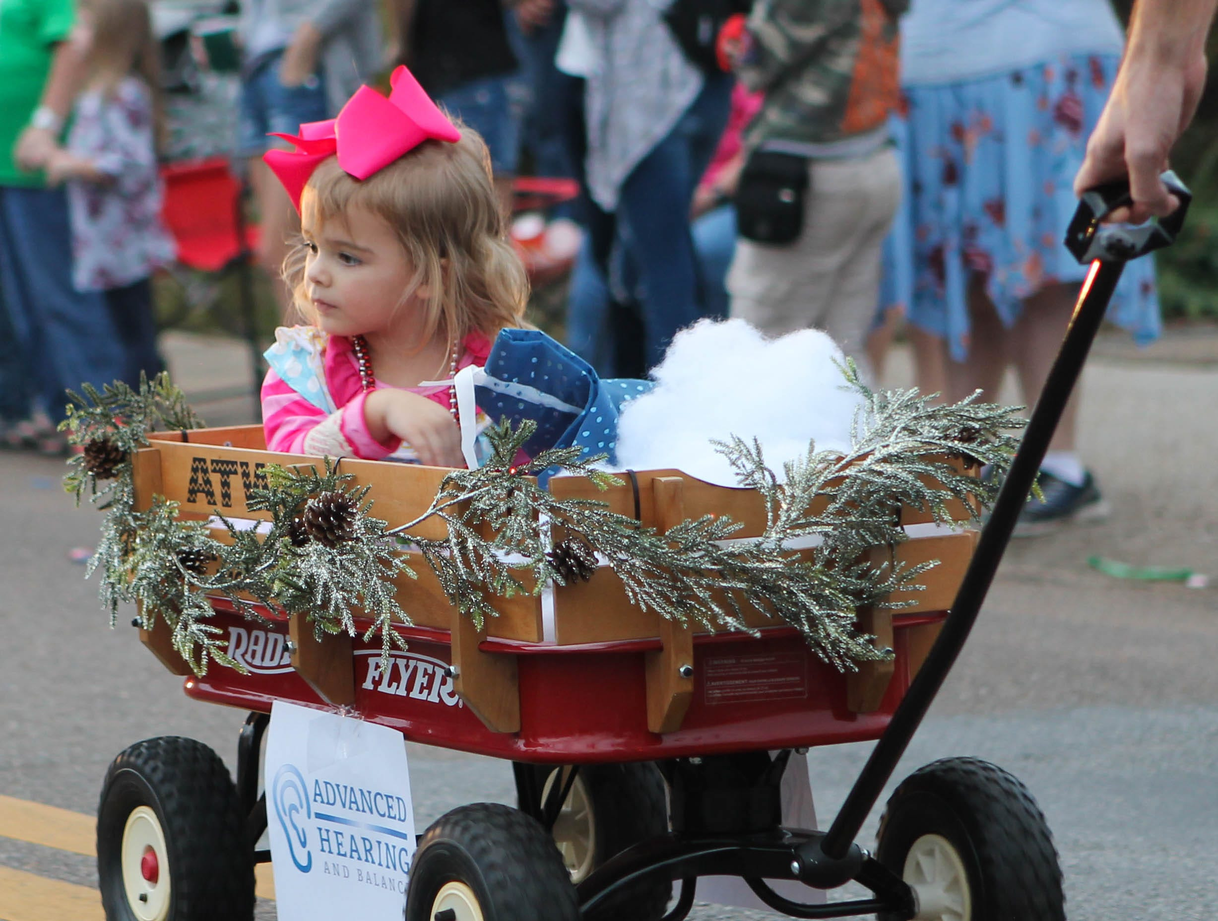 A young girl sits in a wagon while riding in the Petal Christmas Parade on Saturday, December 1, 2018.