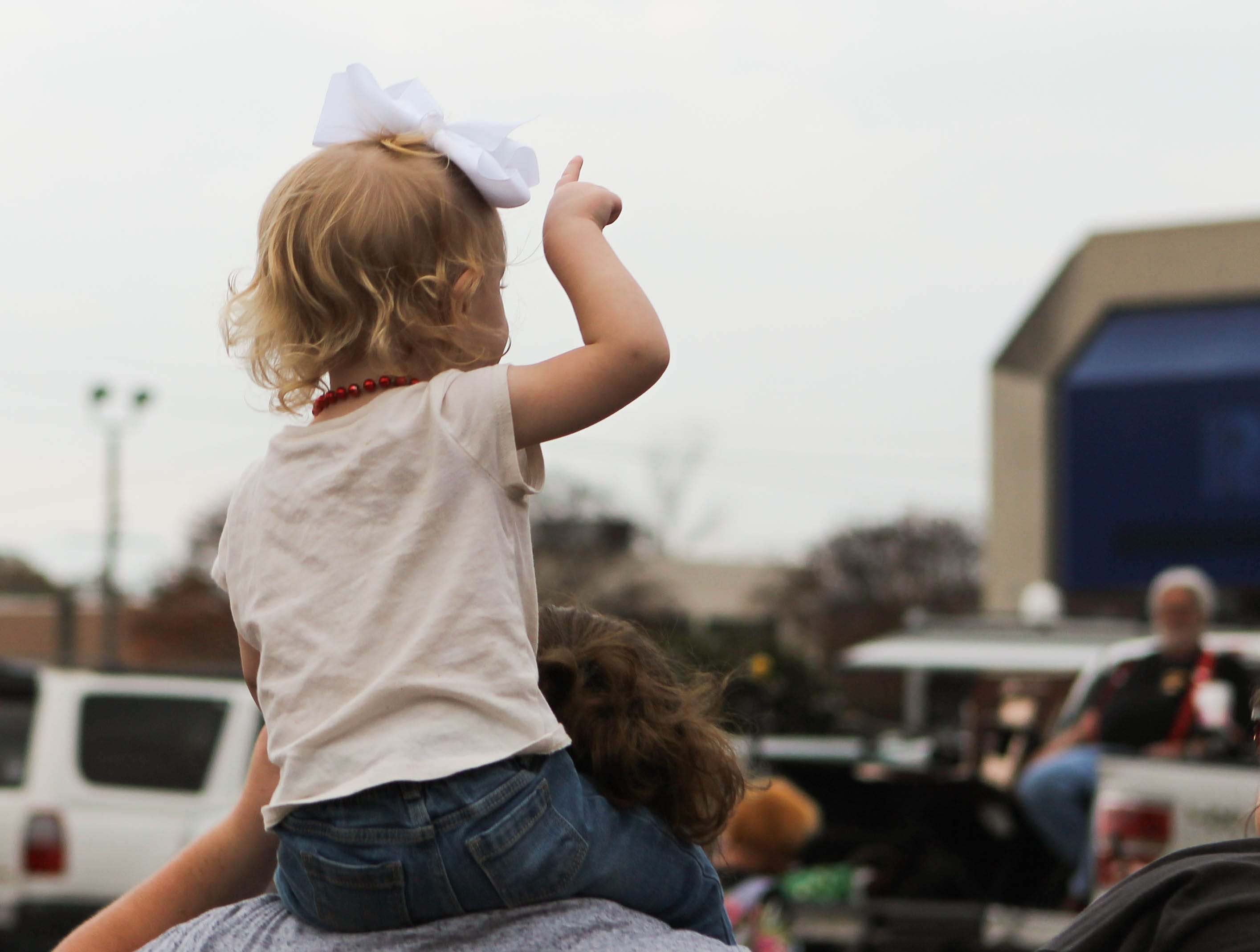 A small child sits on a woman's shoulders to watch the Petal Christmas Parade on Saturday, December 1, 2018.