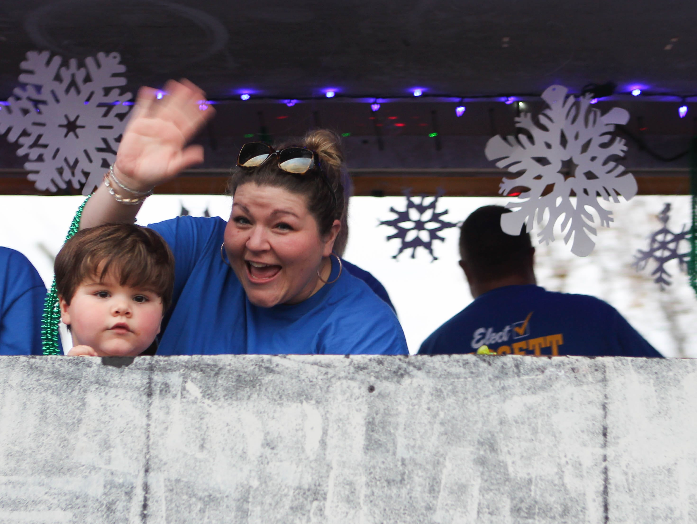 Adrienne Roberts and her son Maddox wave to spectators during the Petal Christmas Parade.