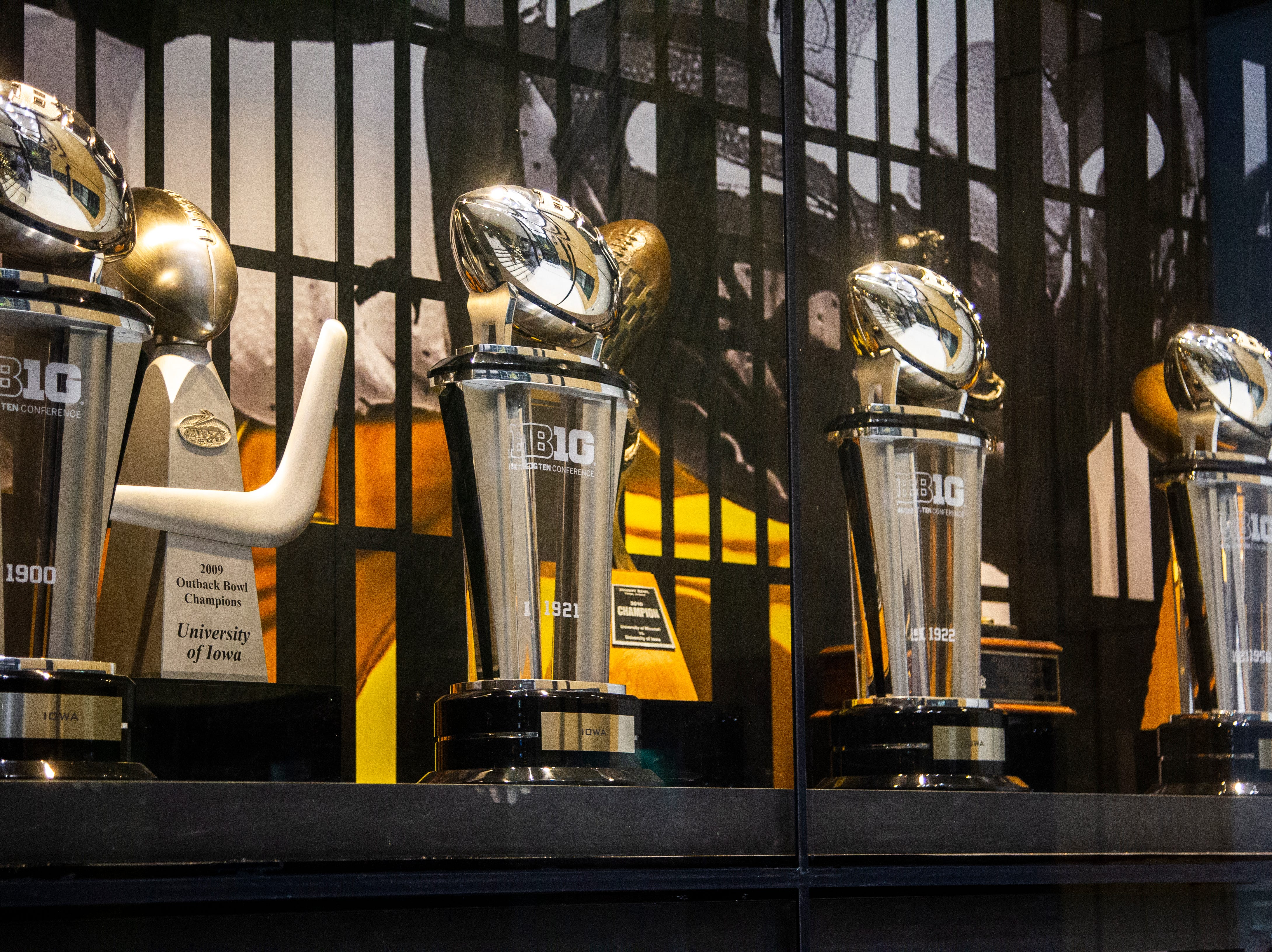 Trophies are displayed inside a case in the lobby including the 1900, 1921, 1922 and 1956 Big Ten Conference Championships, 2009 and 2004 Outback Bowl, 2010 Insight Bowl and 2005 Citrus Bowl, on Sunday, Dec. 2, 2018, at the Hansen Football Performance Center in Iowa City.