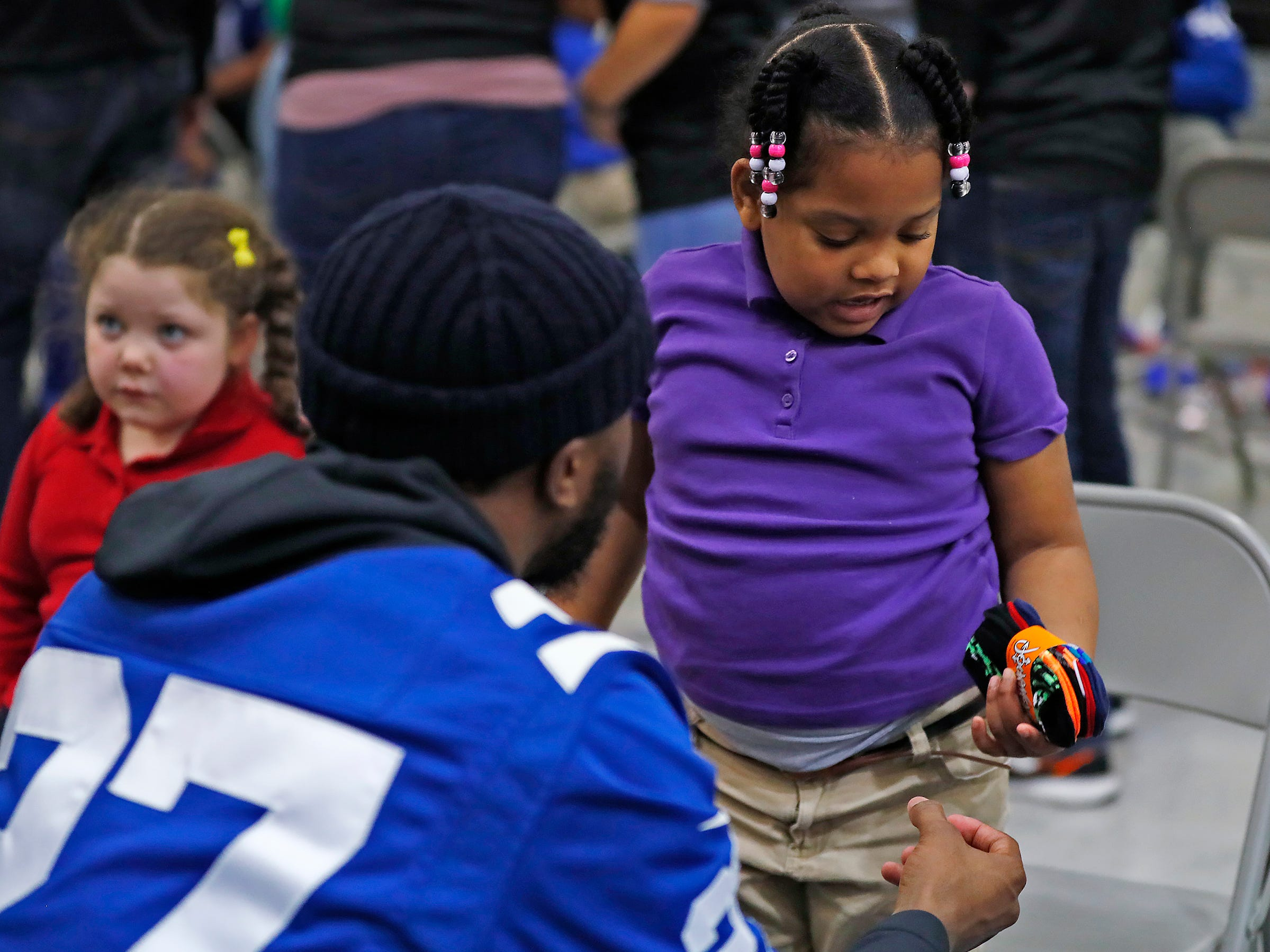 Indianapolis Colts' Nate Hairston gives new socks to Kamoni Bright at Brookside School 54, Monday, Dec. 3, 2018.  Colts players and staff joined as LIDS Sports and its parent company Genesco fit and gave new shoes, socks, hats, and snacks to students as part of the 13th annual Cold Feet, Warm Shoes event.