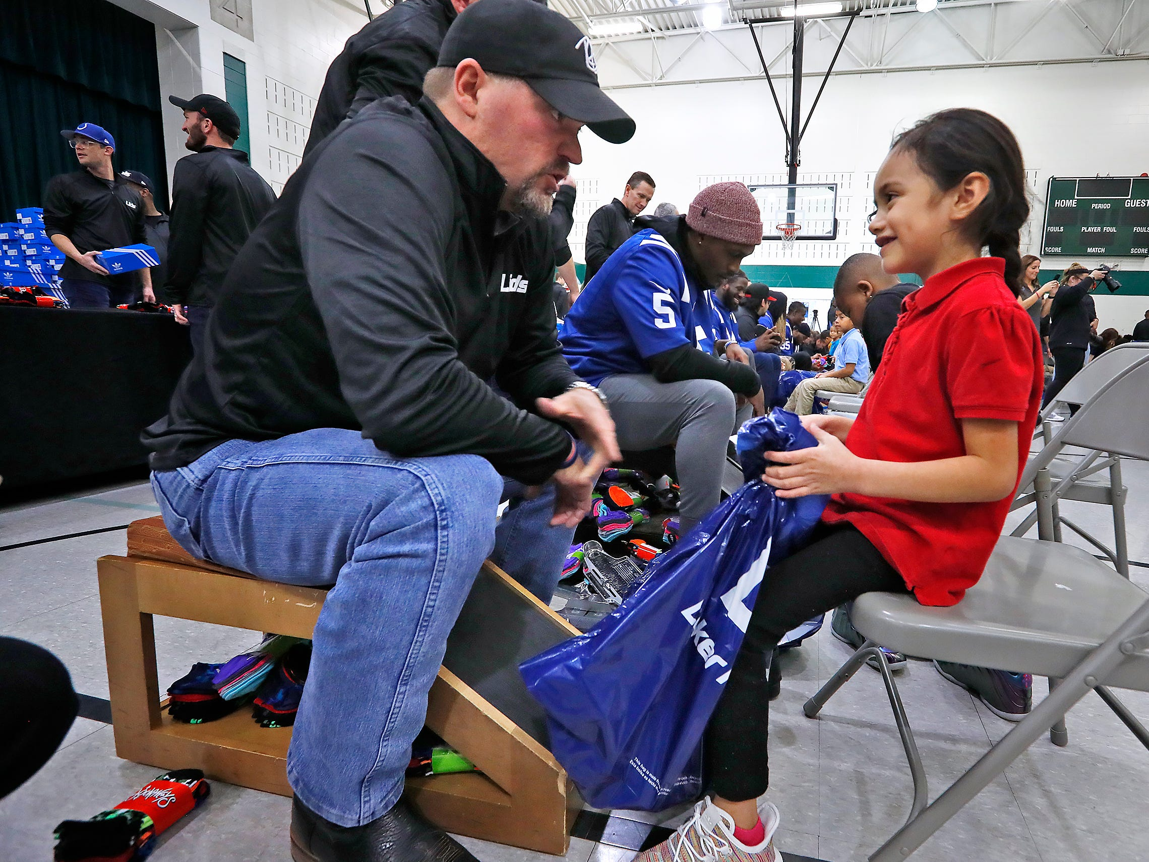 Keith Davis, left, fits Rebeca Perez, right, with a new pair of shoes at Brookside School 54, Monday, Dec. 3, 2018.  Colts players and staff joined as LIDS Sports and its parent company Genesco fit and gave new shoes, socks, hats, and snacks to students as part of the 13th annual Cold Feet, Warm Shoes event.
