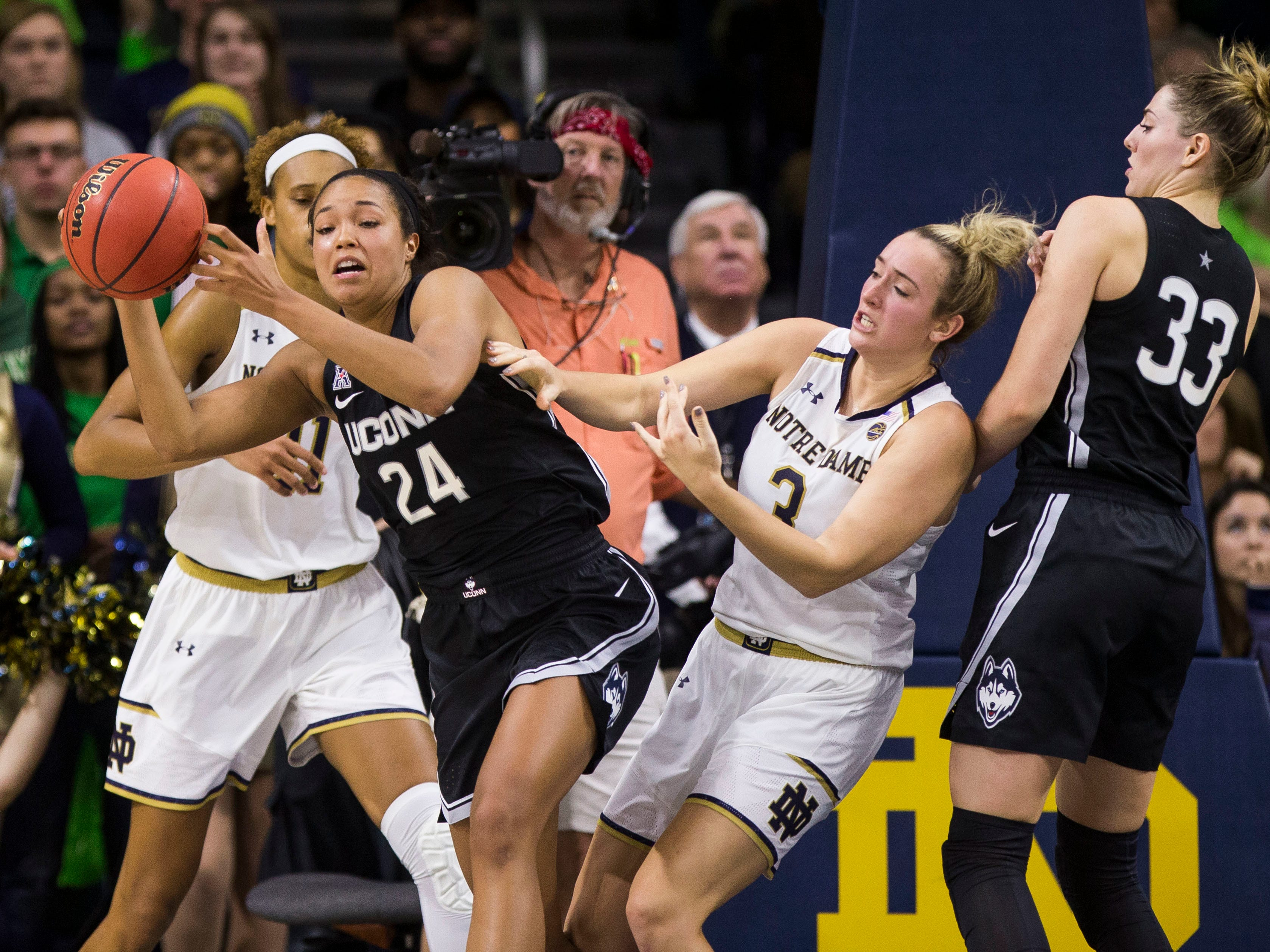 Connecticut's Napheesa Collier (24) passes the ball away after coming down with a rebound between Notre Dame's Brianna Turner, left, and Marina Mabrey (3) during the second half of an NCAA college basketball game Sunday, Dec. 2, 2018, in South Bend, Ind. Connecticut won 89-71.