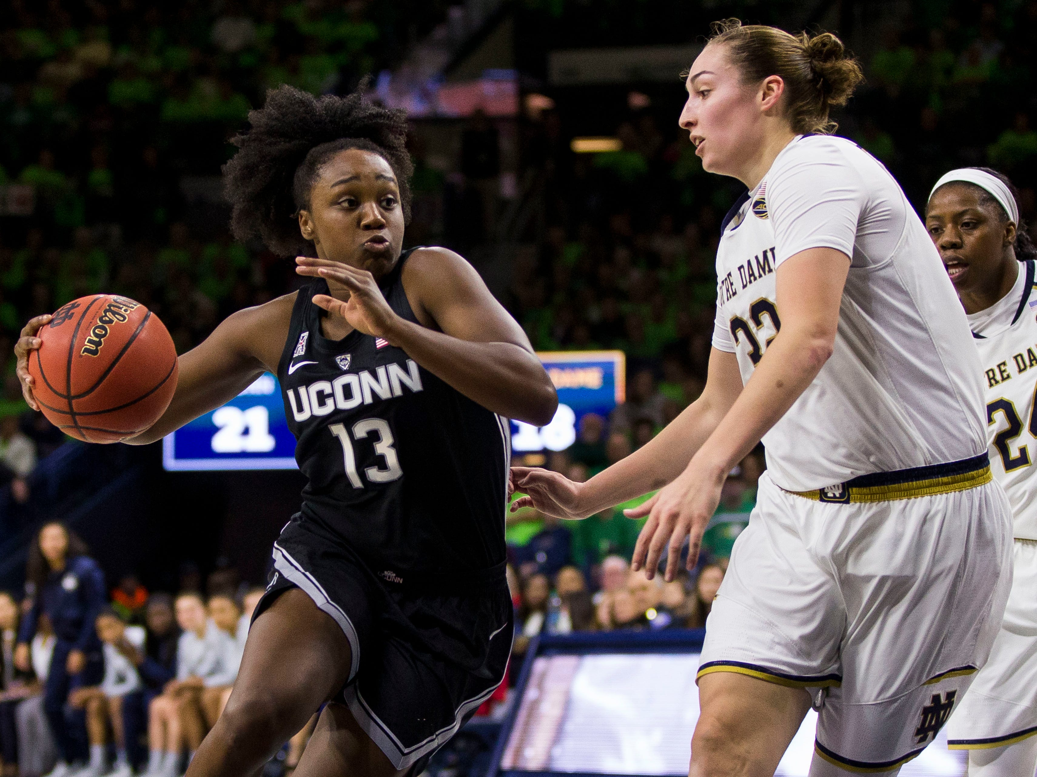 Connecticut's Christyn Williams (13) drives in next to Notre Dame's Jessica Shepard (32) during the first half of an NCAA college basketball game Sunday, Dec. 2, 2018, in South Bend, Ind.