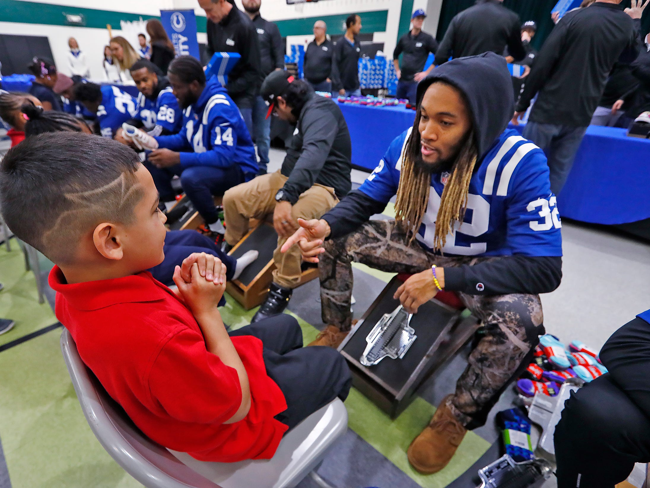 Indianapolis Colts' Jalen Collins talks with Leland Calderon, left, as he fits him for new shoes at Brookside School 54, Monday, Dec. 3, 2018.  Colts players and staff joined as LIDS Sports and its parent company Genesco fit and gave new shoes, socks, hats, and snacks to students as part of the 13th annual Cold Feet, Warm Shoes event.