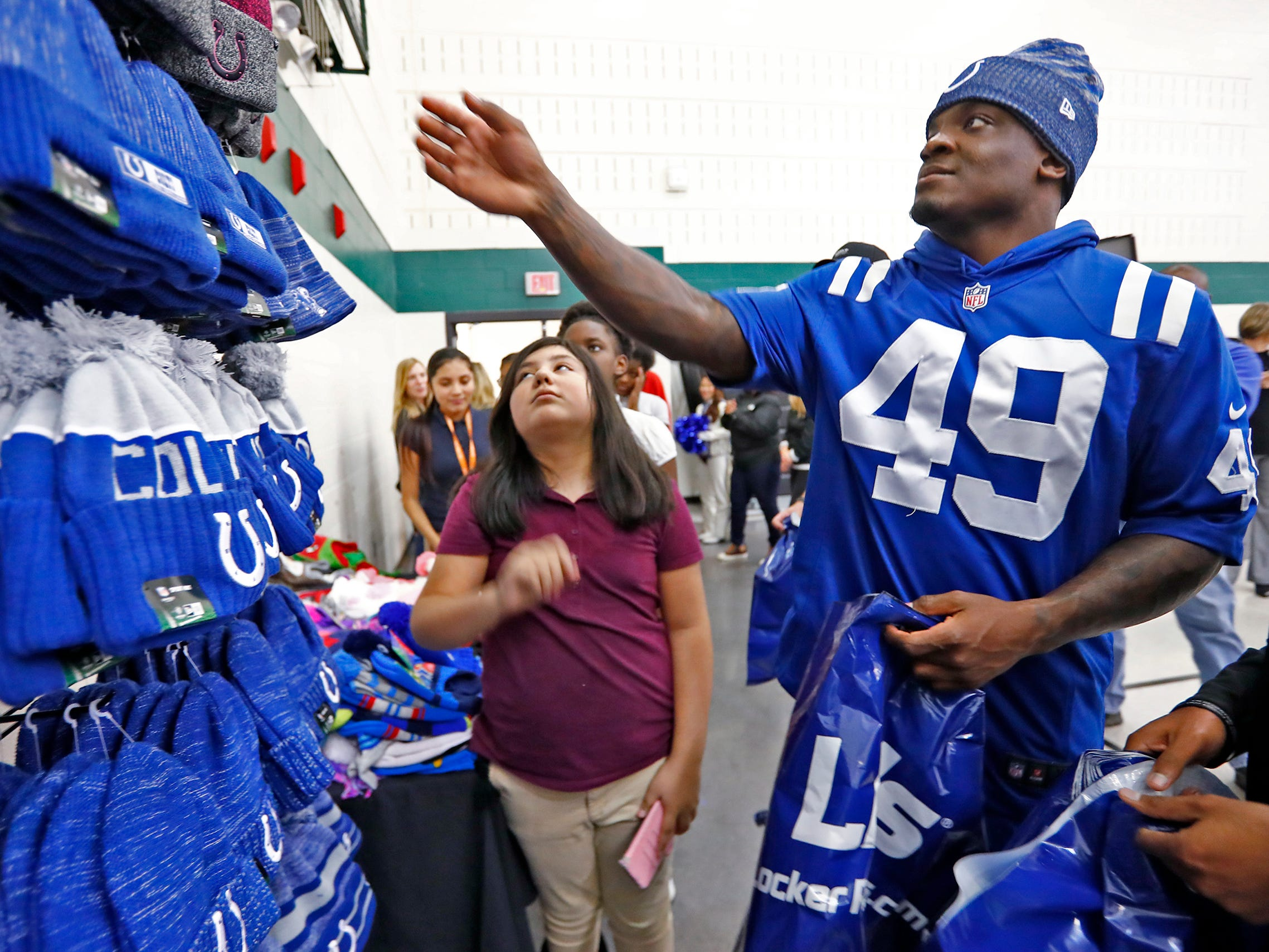 Indianapolis Colts' Matthew Adams reaches for a hat to give to Alicia Martinez at Brookside School 54, Monday, Dec. 3, 2018.  Colts players and staff joined as LIDS Sports and its parent company Genesco fit and gave new shoes, socks, hats, and snacks to students as part of the 13th annual Cold Feet, Warm Shoes event.
