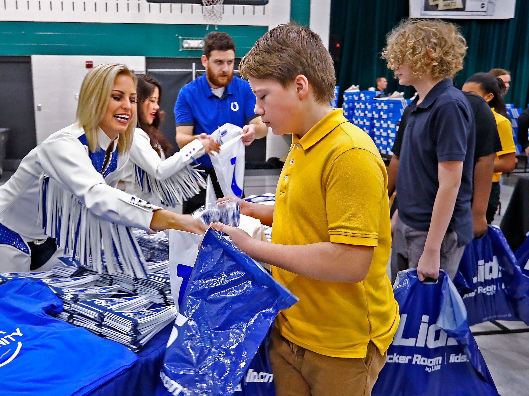 Colts' cheerleader Zhanna, left, and others hand out Colts memorabilia to students, including, Tyler Denton, center, at Brookside School 54, Monday, Dec. 3, 2018.  Colts players and staff joined as LIDS Sports and its parent company Genesco fit and gave new shoes, socks, hats, and snacks to students as part of the 13th annual Cold Feet, Warm Shoes event.