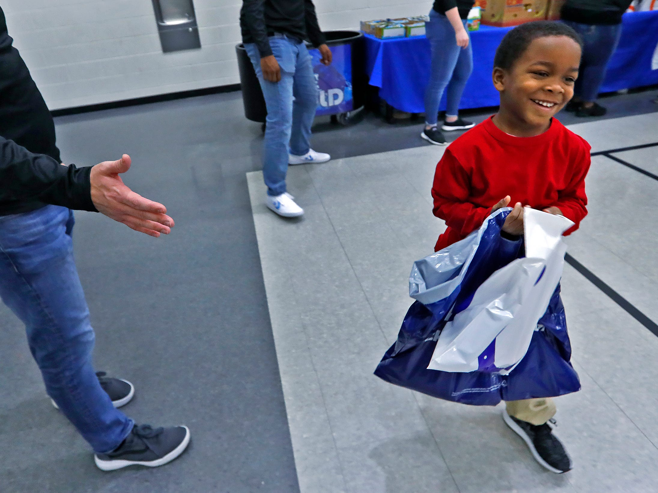 Damoni Lofton smiles after getting shoes, socks, a hat and other gifts at Brookside School 54, Monday, Dec. 3, 2018.  Colts players and staff joined as LIDS Sports and its parent company Genesco fit and gave new shoes, socks, hats, and snacks to students as part of the 13th annual Cold Feet, Warm Shoes event.