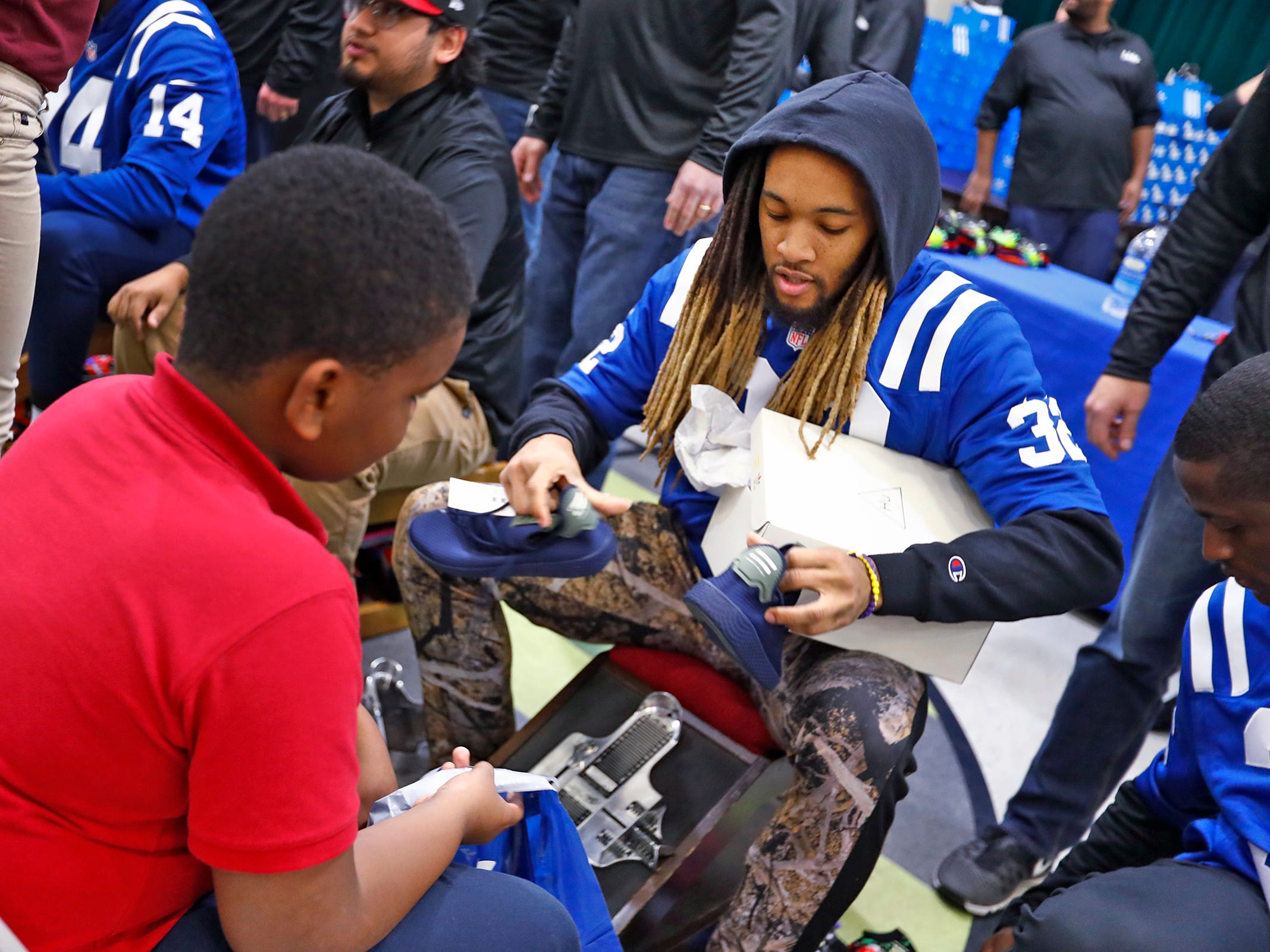Indianapolis Colts' Jalen Collins fits Marquise Sanders for a new pair of shoes at Brookside School 54, Monday, Dec. 3, 2018.  Colts players and staff joined as LIDS Sports and its parent company Genesco fit and gave new shoes, socks, hats, and snacks to students as part of the 13th annual Cold Feet, Warm Shoes event.