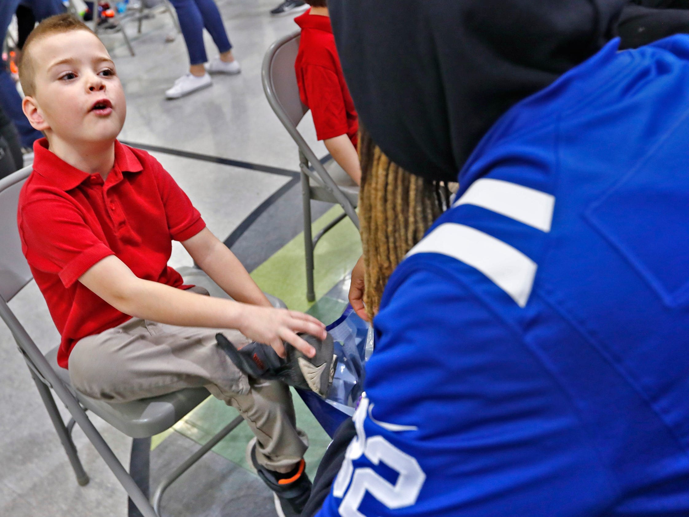 Cody Carter, left, talks with Indianapolis Colts' Jalen Collins while getting fitted for new shoes at Brookside School 54, Monday, Dec. 3, 2018.  Colts players and staff joined as LIDS Sports and its parent company Genesco fit and gave new shoes, socks, hats, and snacks to students as part of the 13th annual Cold Feet, Warm Shoes event.