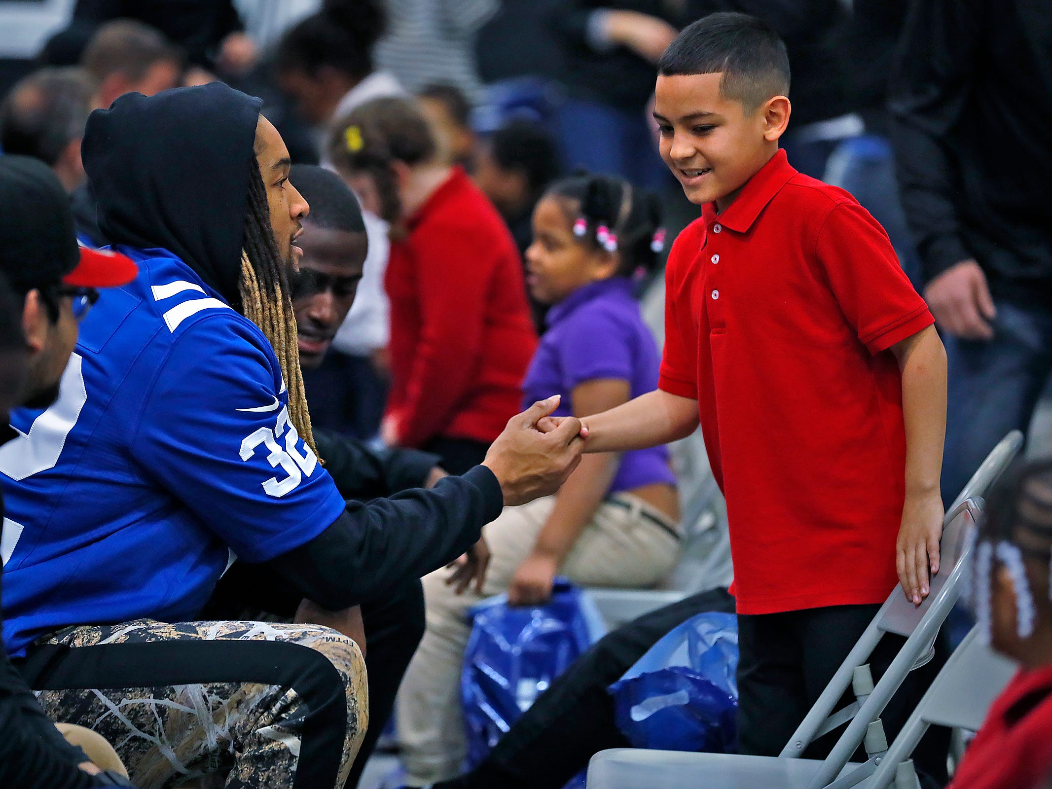 Indianapolis Colts' Jalen Collins shakes hands with Leland Calderon, right, before fitting him for new shoes at Brookside School 54, Monday, Dec. 3, 2018.  Colts players and staff joined as LIDS Sports and its parent company Genesco fit and gave new shoes, socks, hats, and snacks to students as part of the 13th annual Cold Feet, Warm Shoes event.
