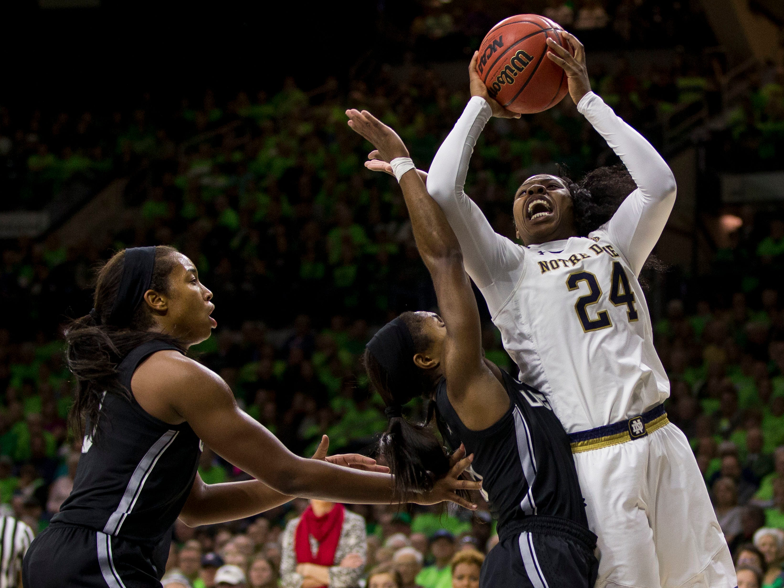 Notre Dame's Arike Ogunbowale (24) shoots over Connecticut's Crystal Dangerfield, center, and Megan Walker during the second half of an NCAA college basketball game Sunday, Dec. 2, 2018, in South Bend, Ind. Connecticut won 89-71.