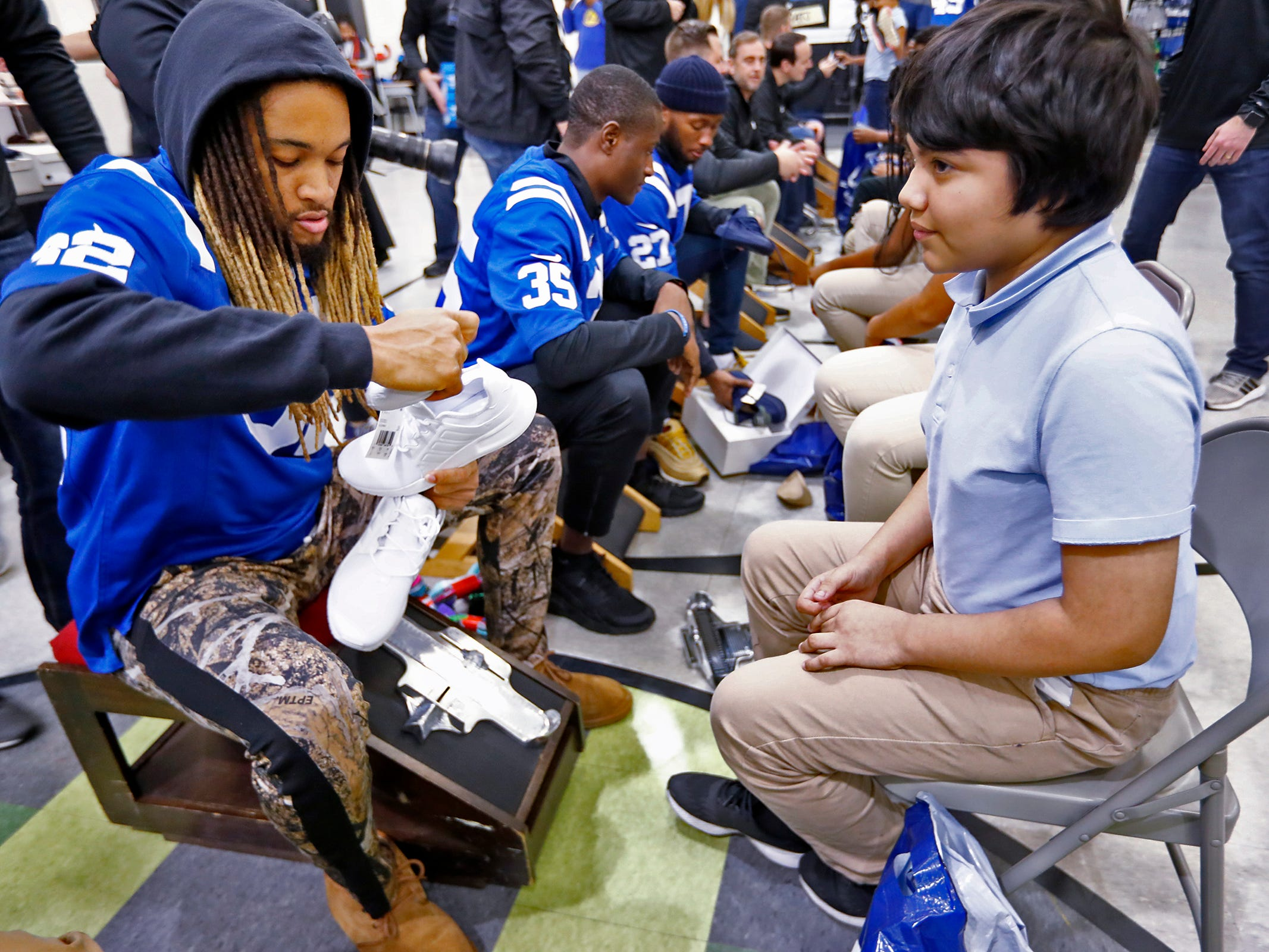 Indianapolis Colts' Jalen Collins fits Adolfo Rodriguez for a new pair of shoes at Brookside School 54, Monday, Dec. 3, 2018.  Colts players and staff joined as LIDS Sports and its parent company Genesco fit and gave new shoes, socks, hats, and snacks to students as part of the 13th annual Cold Feet, Warm Shoes event.