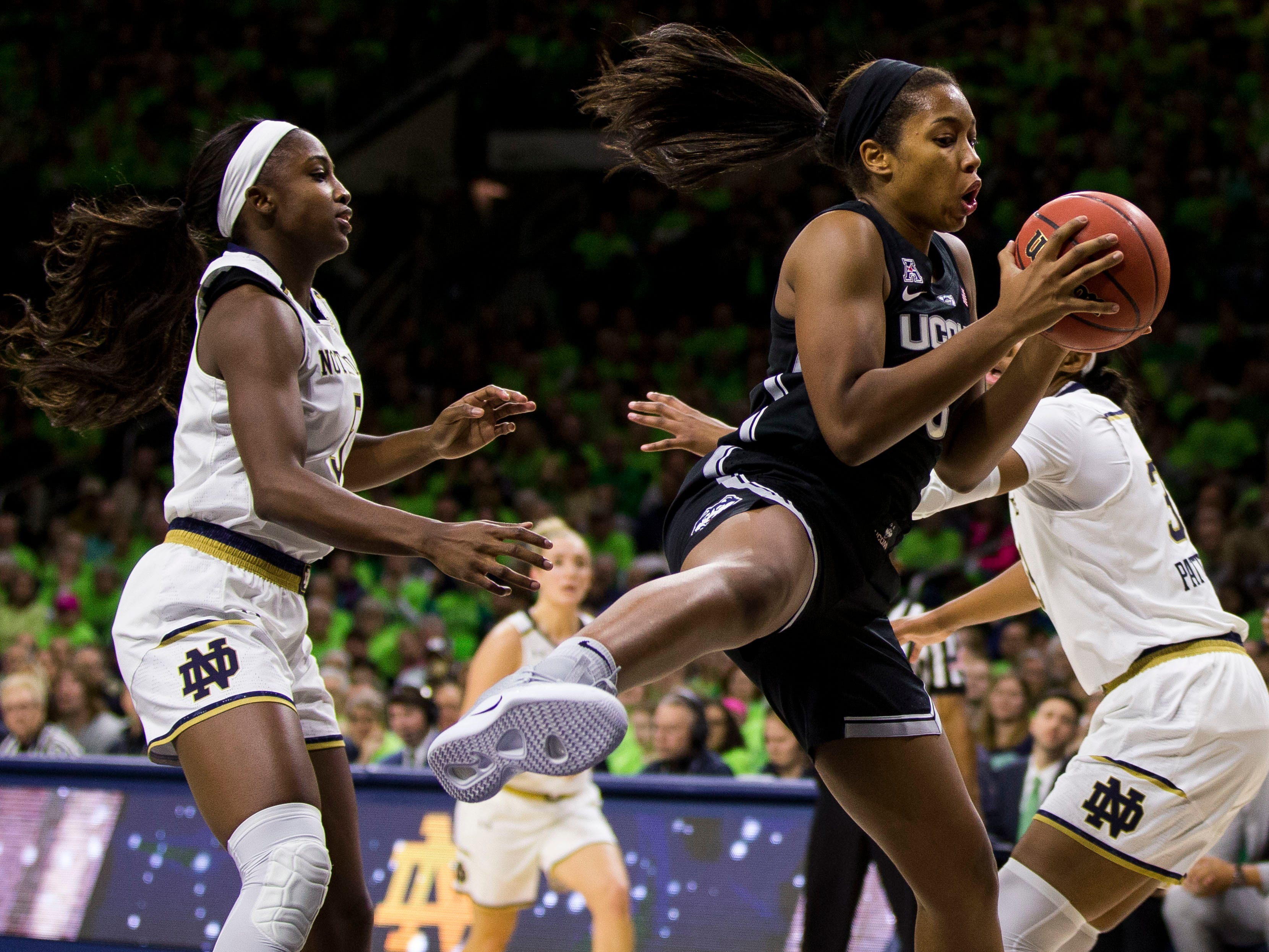 Connecticut's Megan Walker, center, grabs a rebound between Notre Dame's Jackie Young, left, and Danielle Patterson during the first half of an NCAA college basketball game Sunday, Dec. 2, 2018, in South Bend, Ind.