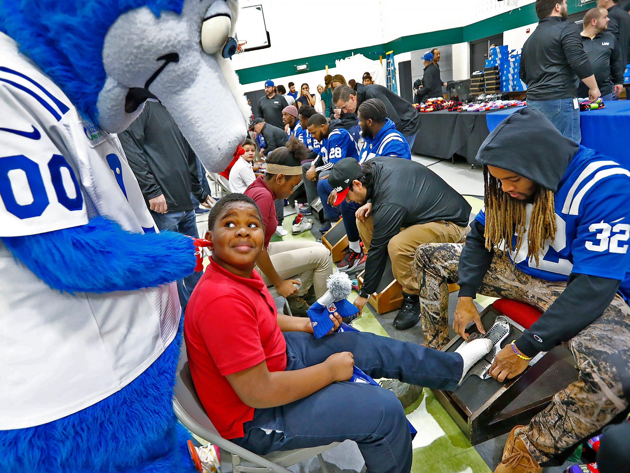 Indianapolis Colts' Jalen Collins fits Marquise Sanders for a new pair of shoes as Colts' mascot Blue teases the student, at Brookside School 54, Monday, Dec. 3, 2018.  Colts players and staff joined as LIDS Sports and its parent company Genesco fit and gave new shoes, socks, hats, and snacks to students as part of the 13th annual Cold Feet, Warm Shoes event.