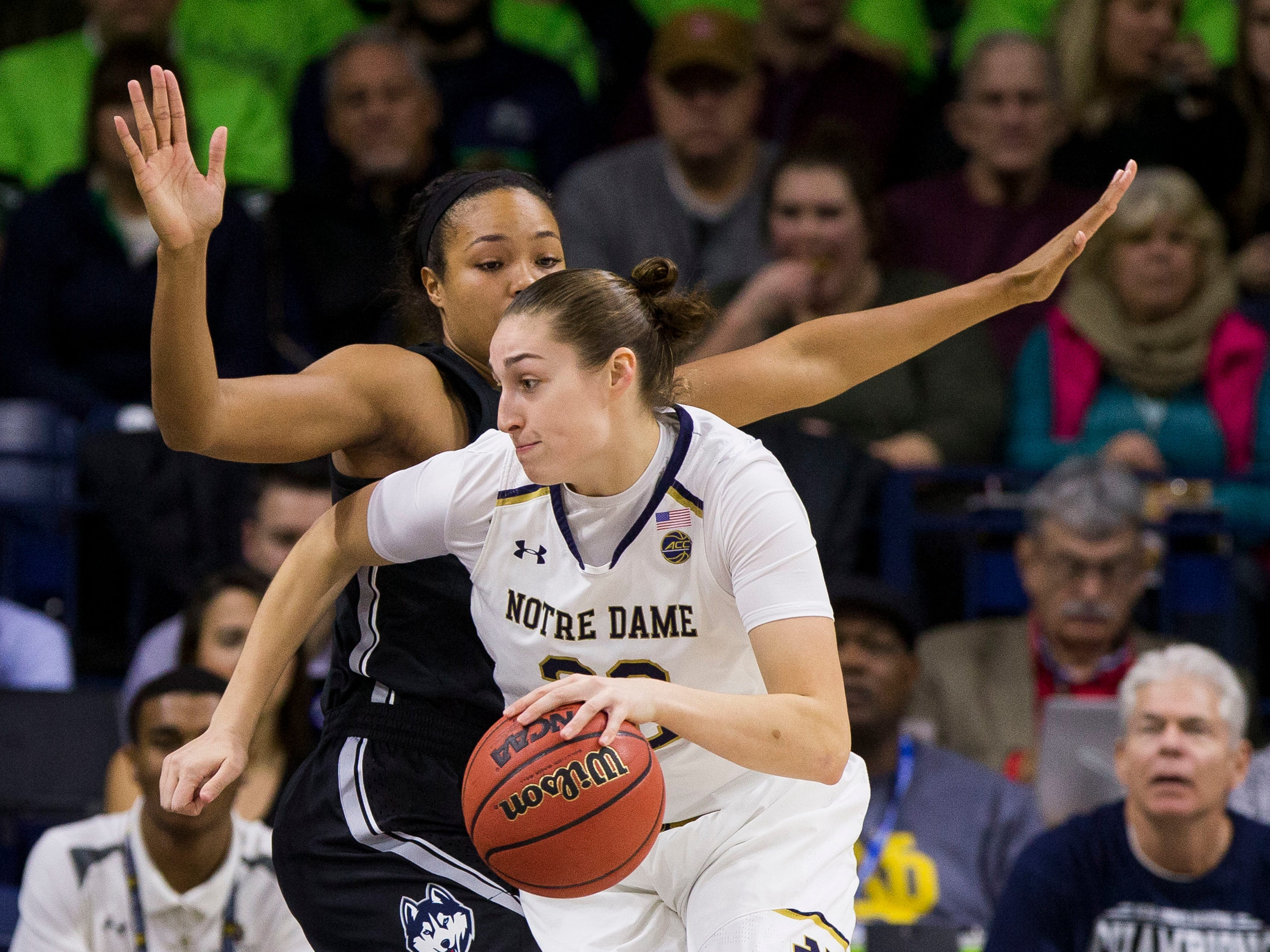 Notre Dame's Jessica Shepard, front, moves by Connecticut's Napheesa Collier during the first half of an NCAA college basketball game Sunday, Dec. 2, 2018, in South Bend, Ind.