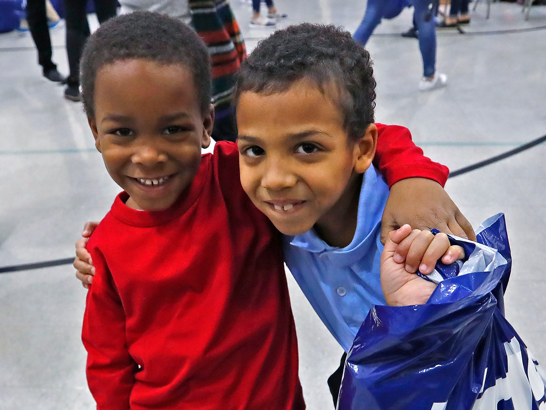 Friends show off their new things, including new shoes, at Brookside School 54, Monday, Dec. 3, 2018.  Colts players and staff joined as LIDS Sports and its parent company Genesco fit and gave new shoes, socks, hats, and snacks to students as part of the 13th annual Cold Feet, Warm Shoes event.
