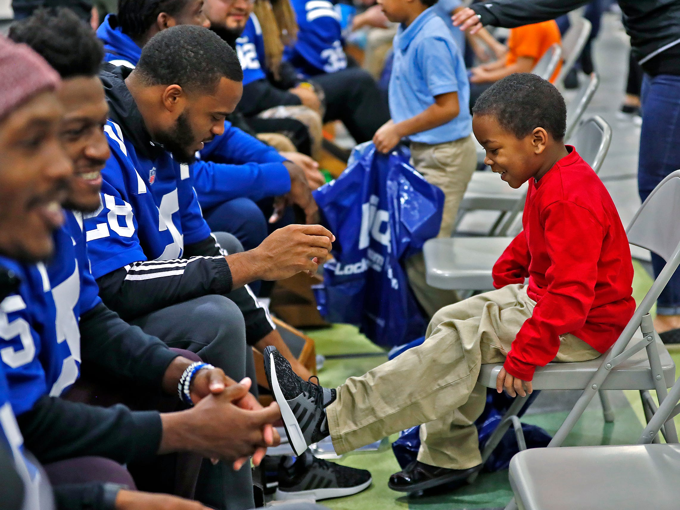 Indianapolis Colts Chris Milton puts new shoes on at Brookside School 54, Monday, Dec. 3, 2018.  Colts players and staff joined as LIDS Sports and its parent company Genesco fit and gave new shoes, socks, hats, and snacks to students as part of the 13th annual Cold Feet, Warm Shoes event.