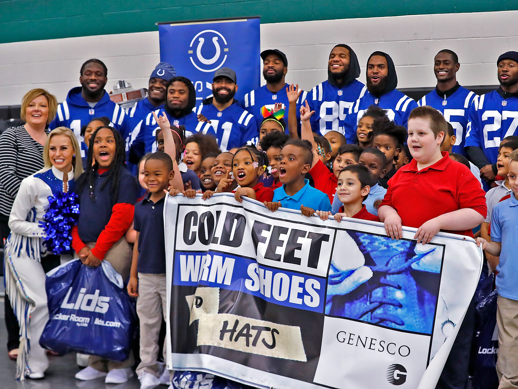 Students, teachers, Colts players, and volunteers pose for  photo after the kids receives new shoes at Brookside School 54, Monday, Dec. 3, 2018.  Colts players and staff joined as LIDS Sports and its parent company Genesco fit and gave new shoes, socks, hats, and snacks to students as part of the 13th annual Cold Feet, Warm Shoes event.