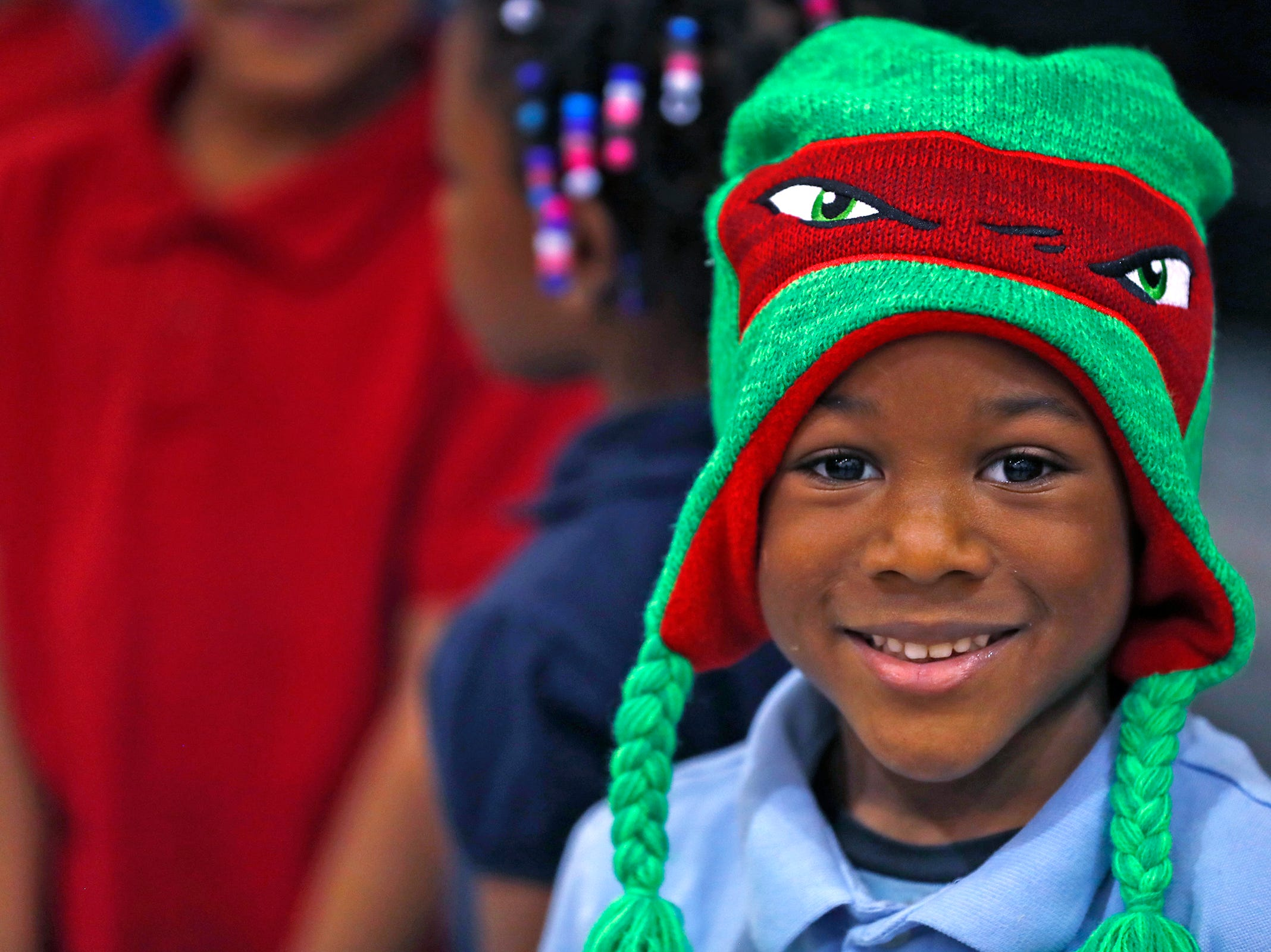 Josiah Beard smiles with his new hat he received at Brookside School 54, Monday, Dec. 3, 2018.  Colts players and staff joined as LIDS Sports and its parent company Genesco fit and gave new shoes, socks, hats, and snacks to students as part of the 13th annual Cold Feet, Warm Shoes event.