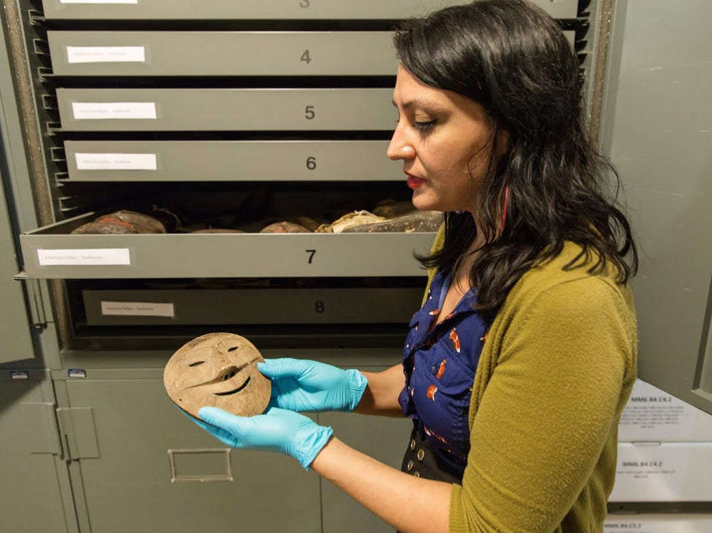 University of Tennessee researcher Christine Dano Johnson shows a Native Alaskan mask Wednesday, June 17, 2015, at the McClung Museum of Natural History and Culture. Johnson, a rising UT senior, has spent several summers researching the origins of McClung's Alaskan artifacts.