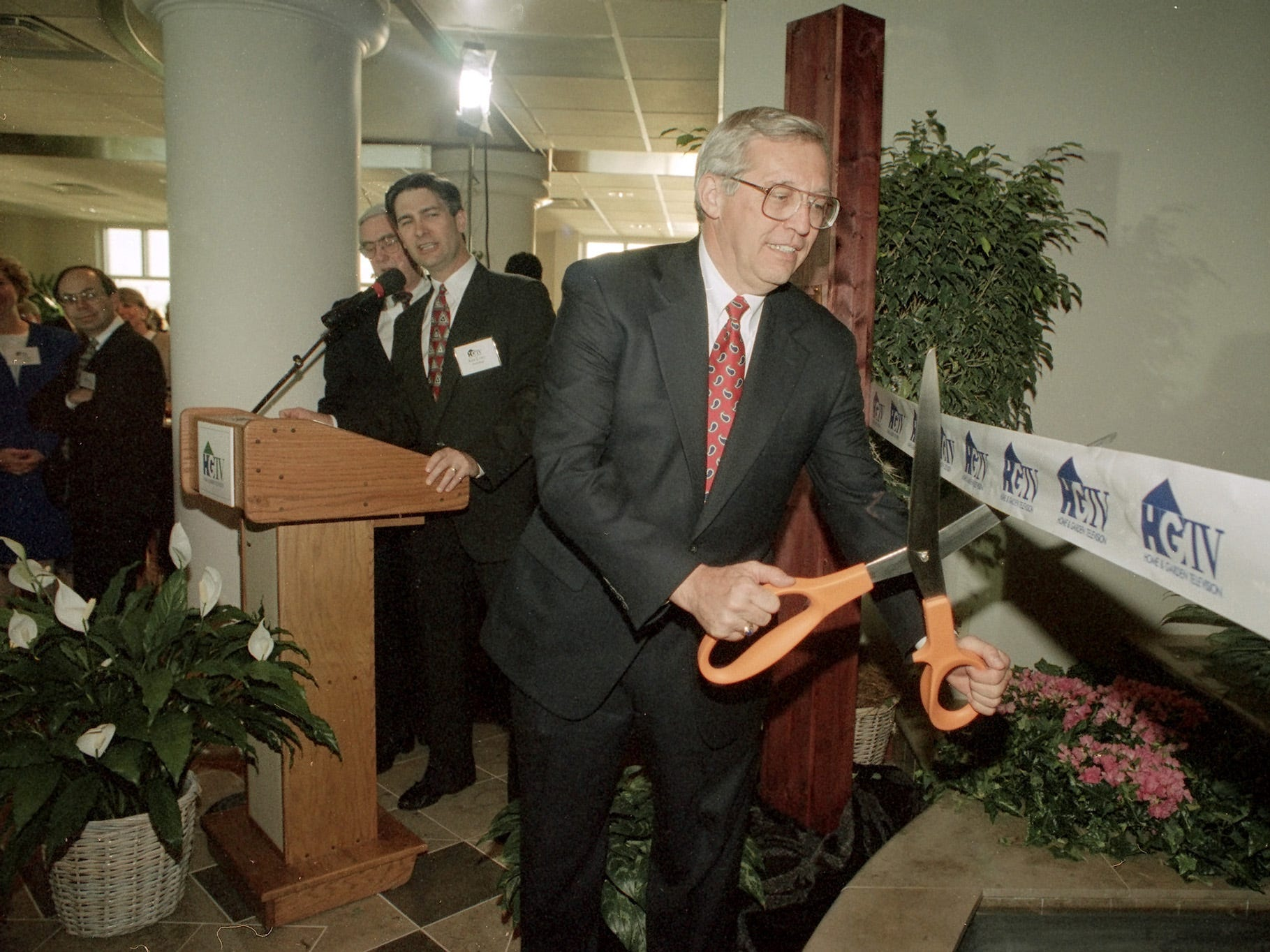 Gov. Don Sundquist cuts the ribbon on Home & Garden Television's new 44,000-squae-foot building on Monday night. Lawrence Leser, far left, chairman and chief executive officer of the E.W. Scripps Co., flipped the switch at 7 p.m., activating the first transmission from the Knoxville facility.  At center is Ken Lowe, president  of HGTV.