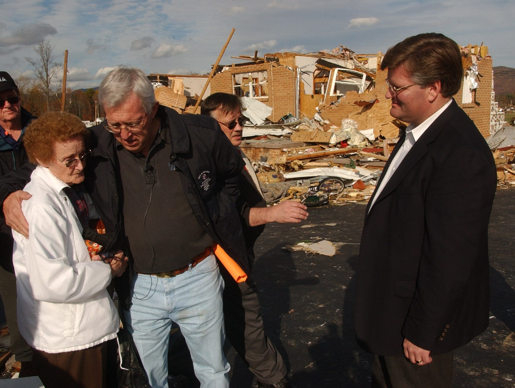 Macel Phillips gets a hug from Tennessee Governor Don Sundquist Monday afternoon in front of her tornado damaged home in the Mossy Grove community  of Morgan County.  Governor Sundquist traveling with a troop of officials was touring the storm damaged areas of the state.   Tommy Kilby (right)  Morgan County Executive looks on.