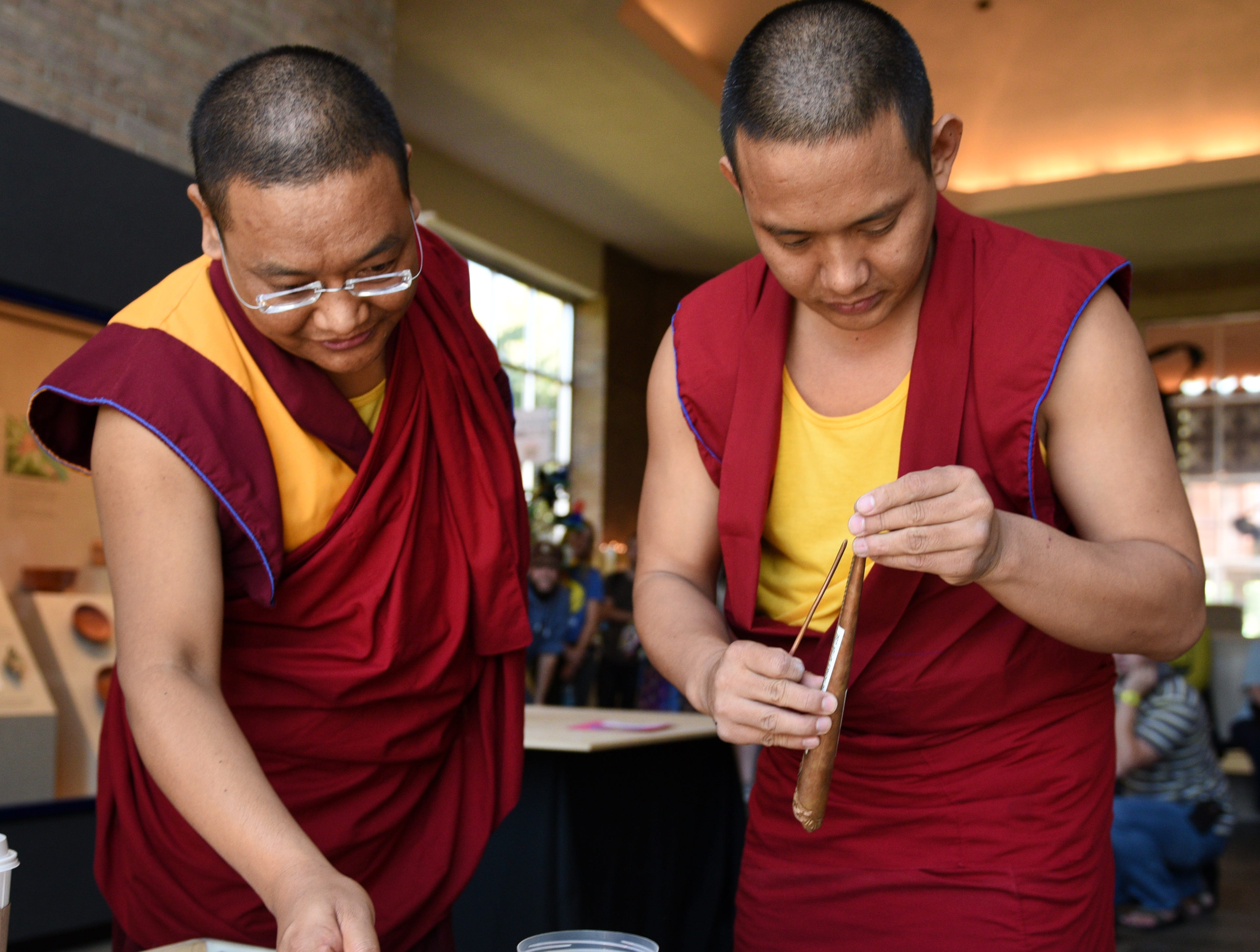 Tibetan Buddhist monks Geshe Thupten Loden, left, and Lobsang Tashi prepare elements for the community sand mandala painting at the McClung Museum Tuesday, Sep. 22, 2015. They chanted during an opening ceremony before starting their sand mandala in another room.