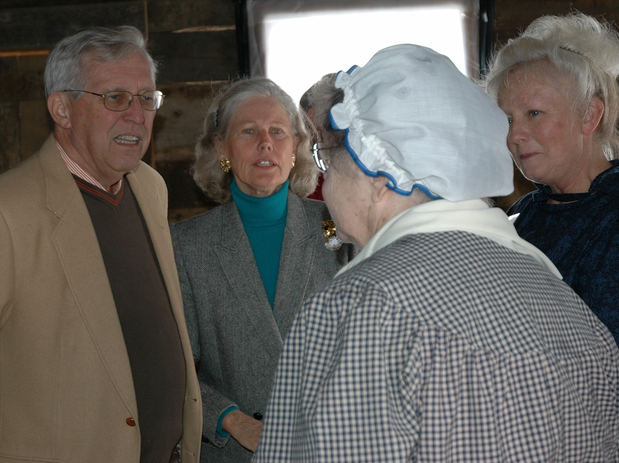 Former Tennessee Gov. Don Sundquist and his wife, Martha, talk with Gaynelle Kyser and Ruth Davis, who were conducting cooking demonstrations in the Cardwell cabin at the new Great Smoky Mountains Heritage Center in Townsend. The center held its grand opening Sunday, 2.12.06. The former governor, now a resident of Townsend, is on the center's board of directors. 2006