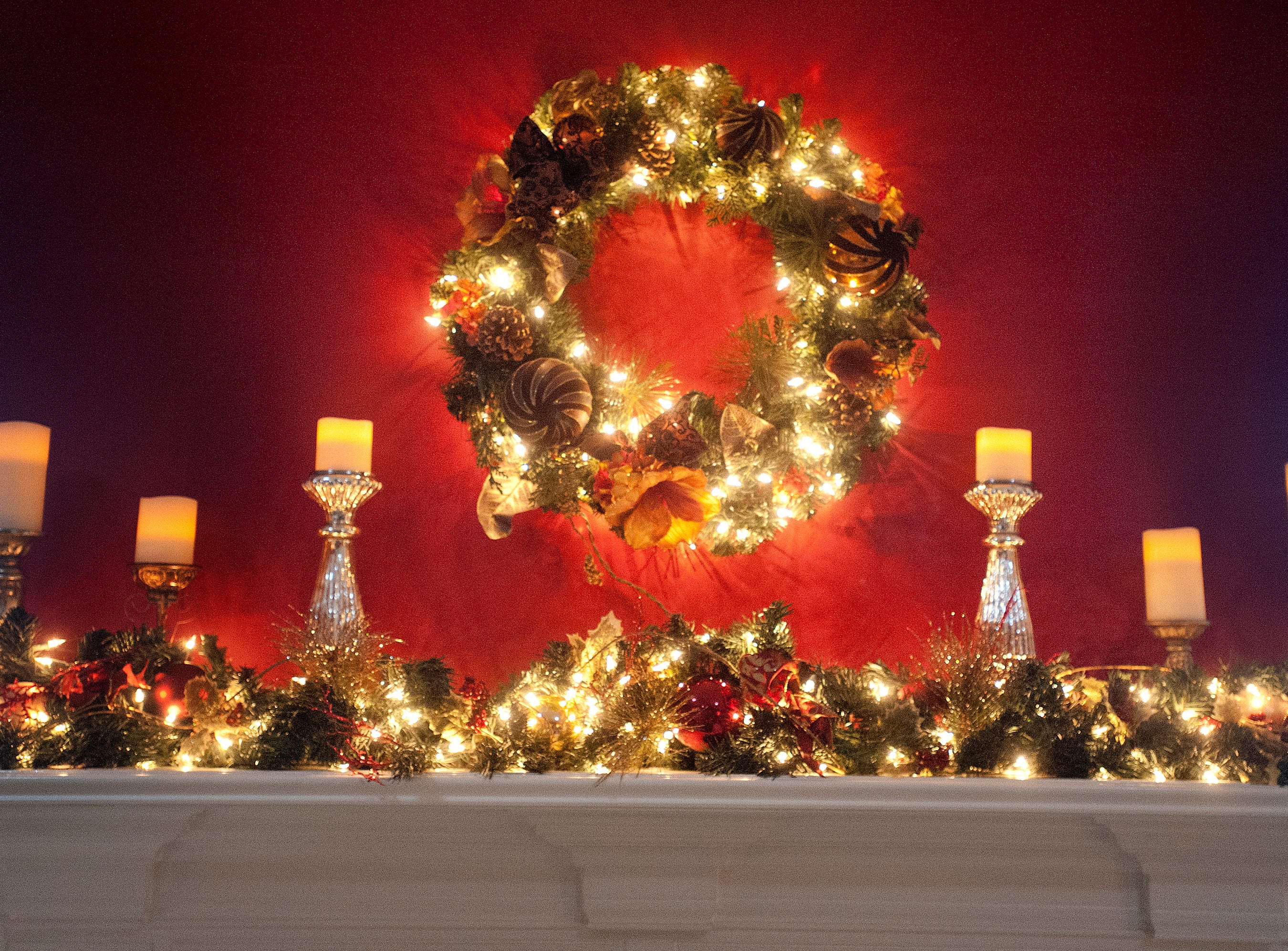 Candles and an illuminated wreath decorate the living room mantel. 