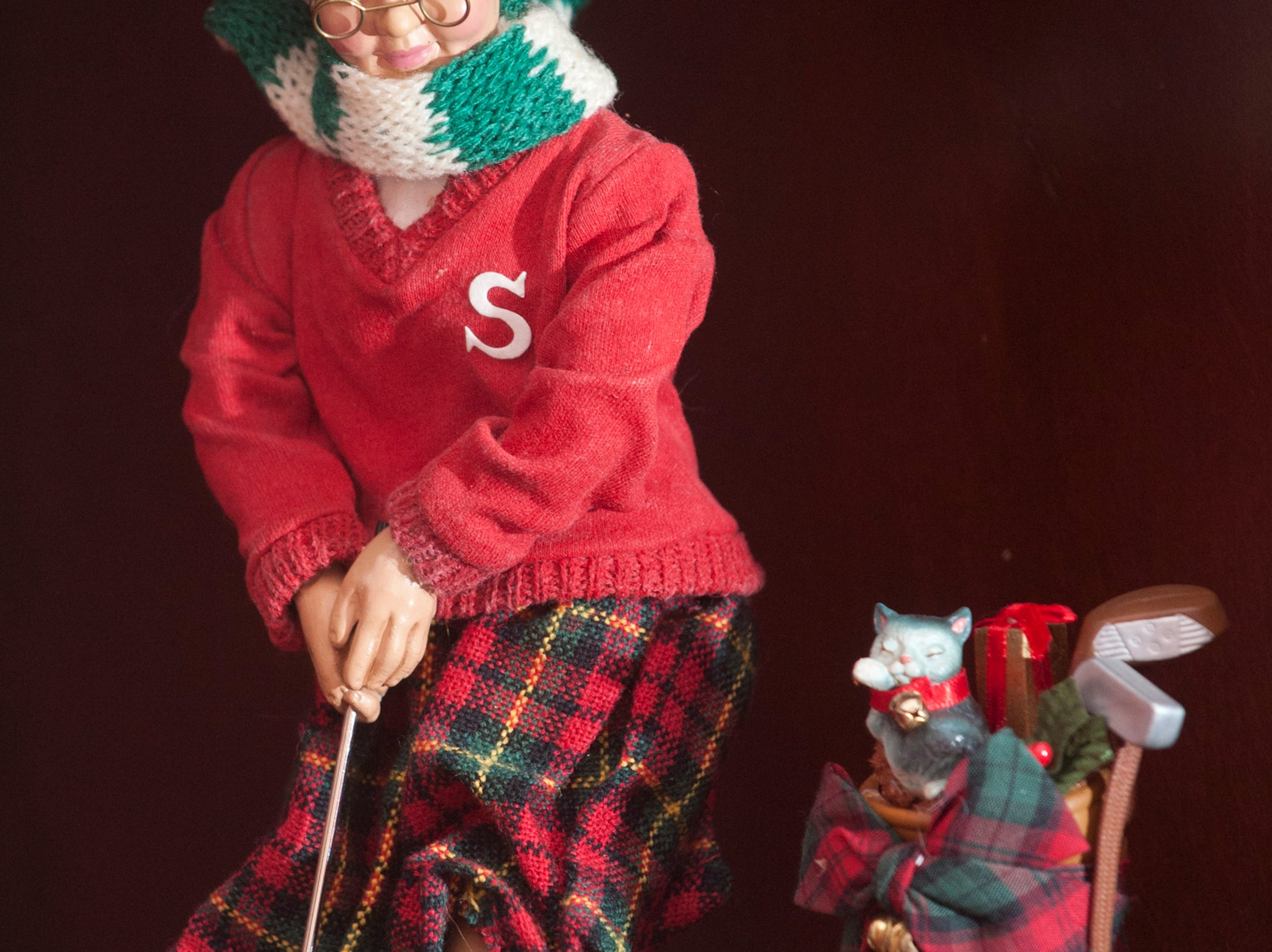 This figurine of Mrs. Santa includes a little kitten popping out of her golf bag.