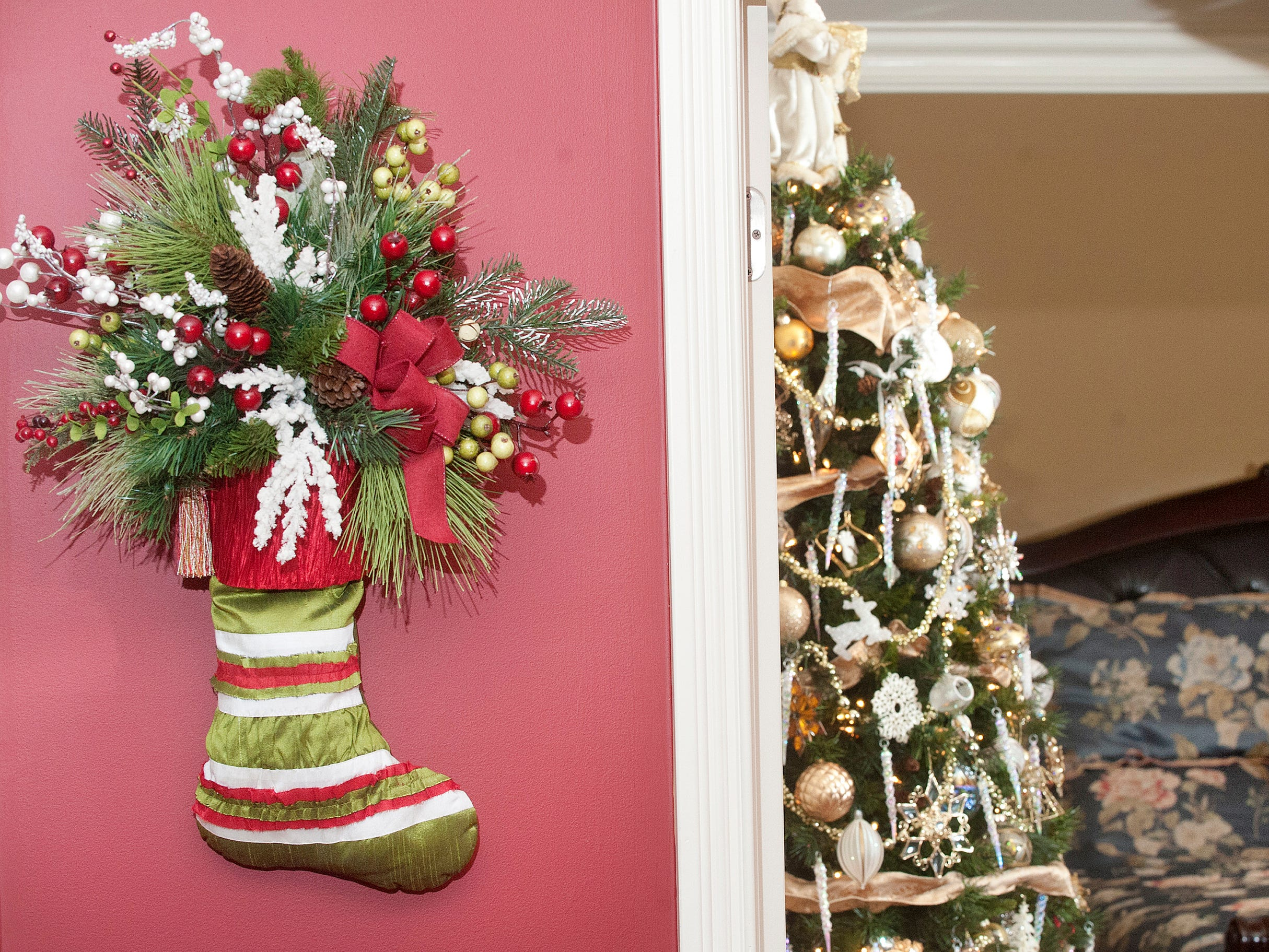 A stocking filled with greenery and berries adorns the wall outside the entrance to the master bedroom at right.