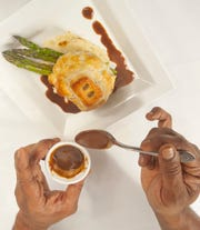 "Buck's Restaurant and Bar Executive Chef Allen Sims' short rib Wellington started with braised short ribs that are encased with a chicken pate inside a puff pastry (who's top is shaped in the letter ""B,"" for Buck's.) The dish is finished with a beef demi-glace and served with asparagus.