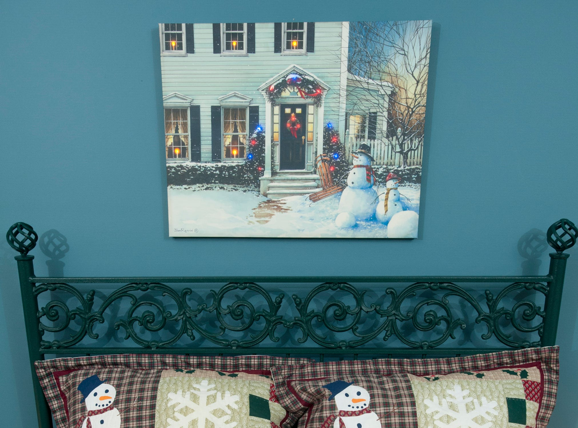 A Christmas season bed quilt, pillows and painting decorate the guest room of the McMurry home.
