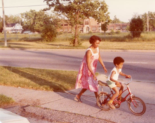Jessie Richardson, left, with grandson Tyrone Gridiron (3), in front of their home on St. Joseph and Everett. The photo was taken after the demolishing in 1965-1966 of more than 600 homes in the area. Photo was taken just prior to the beginning of construction. Across the median the Main Street School can be seen.