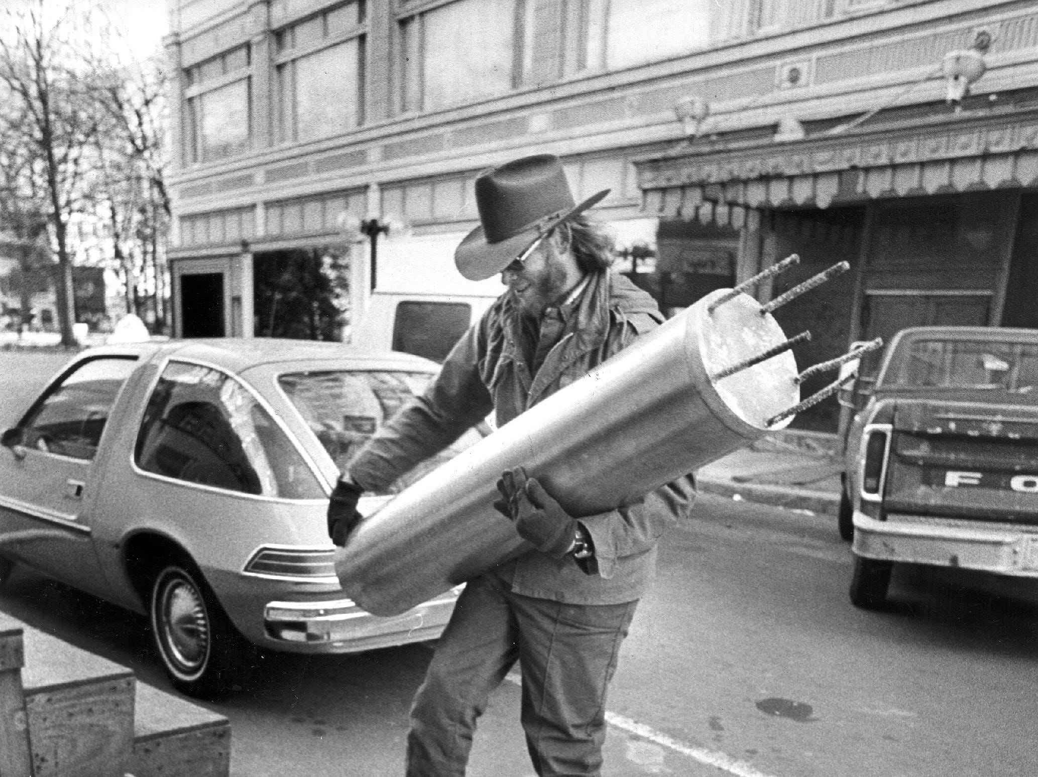 Larry Rush, of Rush Engineering, the company that built the Mid-America Mall, carries a Sesquicentennial time capsule near the Exchange Building and Court Square on 20 Dec 1976.  The capsule had been planted in the Civic Center Plaza in 1969 and was to have been opened in time for the city's bicentennial observance in 2019.  It had been removed when construction began on the Mid-America Mall and had been missing for about six months when it turned up at the mall construction office.  The capsule, containing mementos of the sesquicentennial, was to be reset in the completed plaza.