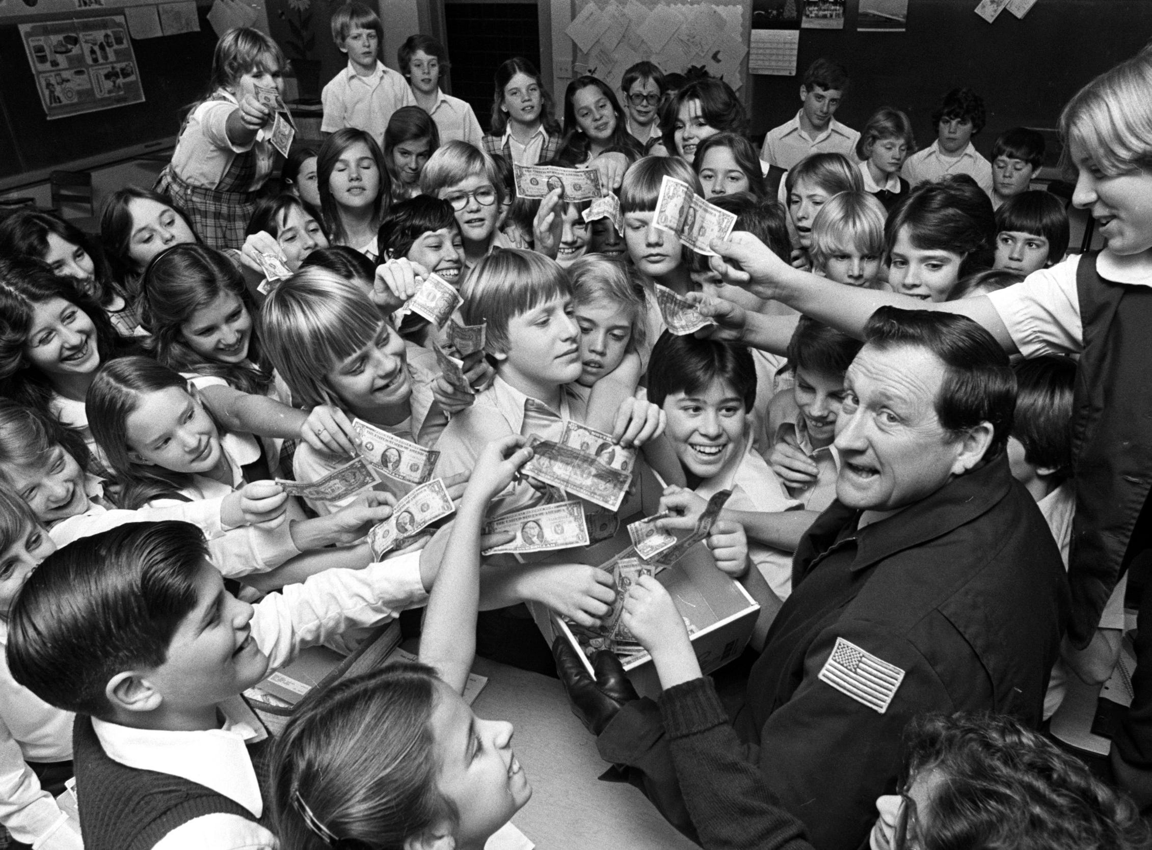 Fire Department Lt. Bob Lyles (Right Foreground) received $100 in donations for the March of Dimes from sixth graders at Holy Rosary School on 18 Dec 1978.  The money was raised by baking and selling cakes, cupcakes and other goodies.
