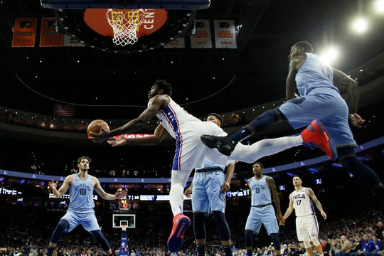 Philadelphia 76ers' Joel Embiid, center, goes up for a shot past Memphis Grizzlies' JaMychal Green during the first half of an NBA basketball game, Sunday, Dec. 2, 2018, in Philadelphia. (AP Photo/Matt Slocum)