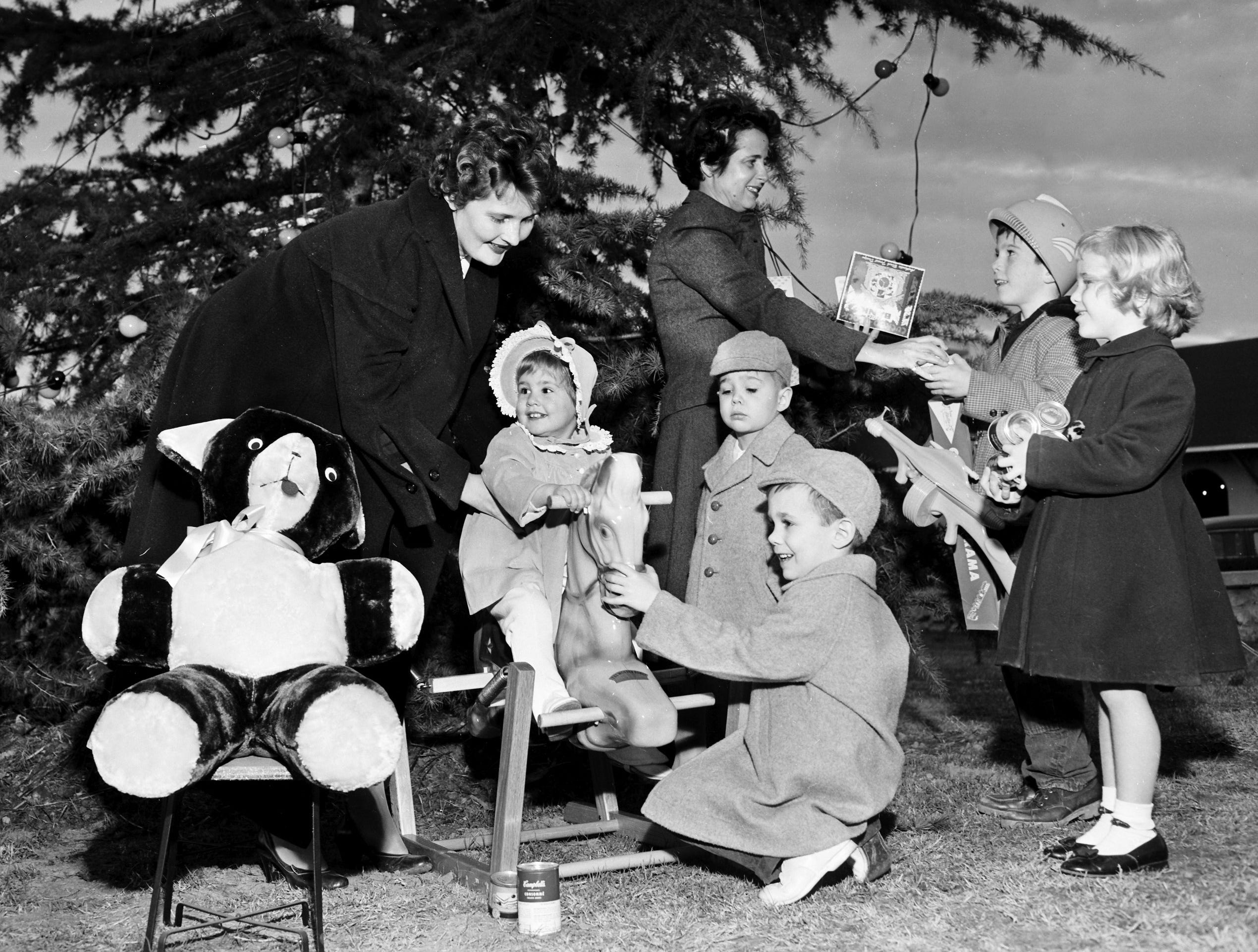 Several children visited Thomas A. Edison Park at Madison and Lauderdale on 18 Dec 1954, including (From Left) Virginia Campbell, Snowden Todd, Hardy Todd III, Frank Crump III and Roder Crump.  They were there to see the Children's Christmas Tree, which was to be dedicated the following day.  The children were accompanied by Mrs. George Campbell (Left) and Mrs. Frank Crump Jr., president of the Junior League of Memphis Garden Club, sponsor of the tree.