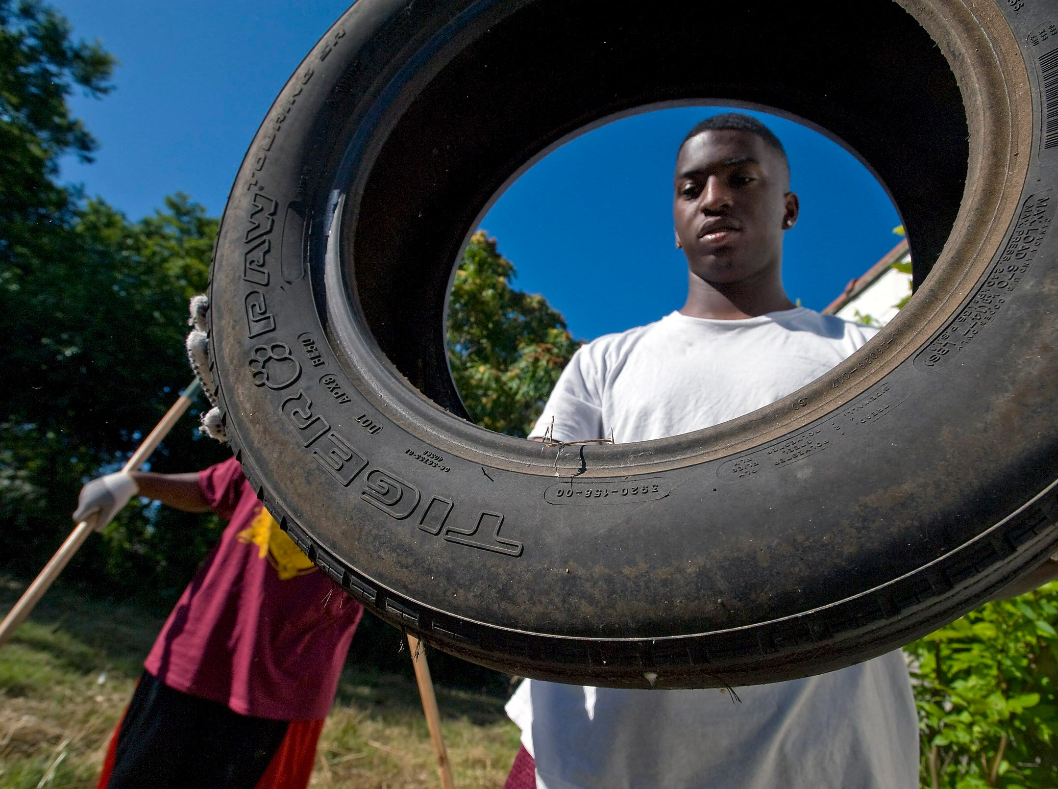 Calvin Alford, 17, a student at Melrose high school carries old tires from around an abandoned building off Park Ave. Over 40 volunteers, children, teens and adults from local schools and church groups spent their Saturday morning where they combined their efforts to clean up their neighborhood near the Melrose football stadium and the Orange Mound Community Center.