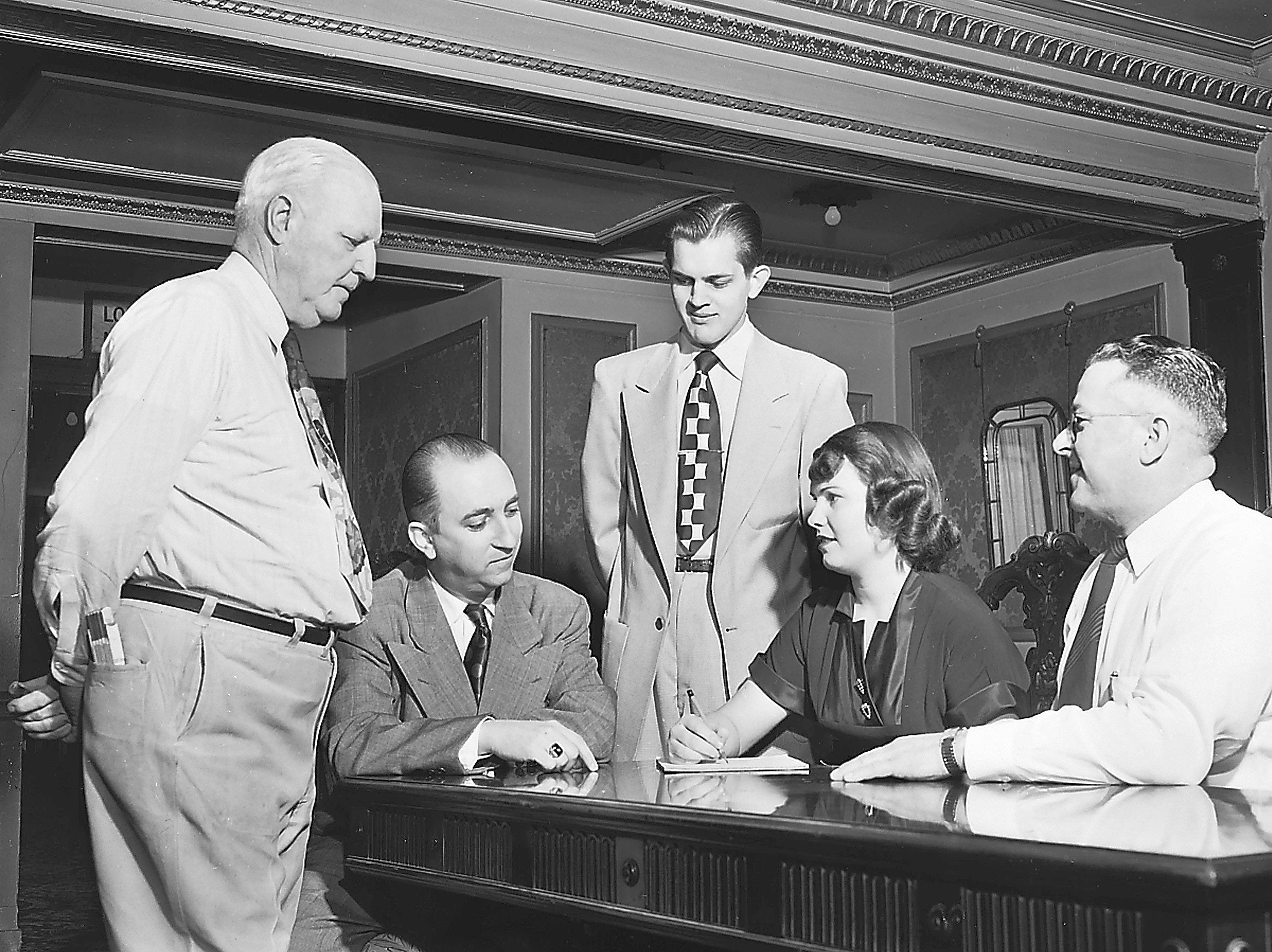 Getting together in December 1952 for a final huddle to see that the 20th annual Midnight Revue goes off smoothly at Loew's State were members of the theater's staff — (From Left) Charles Seiler, stage manager; Arthur Groom, theater manager; Charles Rickard, assistant manager; Ethel Martin, secretary, and Jack Carter, engineer.  For all but Mr. Groom, who is a veteran on these stage-screen benefit shows, it will be the first Midnight Revue in which they have taken part.