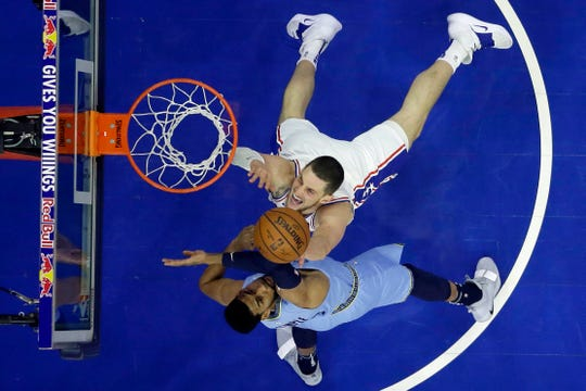 Philadelphia 76ers' Mike Muscala, top, tries to shoot past Memphis Grizzlies' Garrett Temple during the first half of an NBA basketball game, Sunday, Dec. 2, 2018, in Philadelphia. (AP Photo/Matt Slocum)