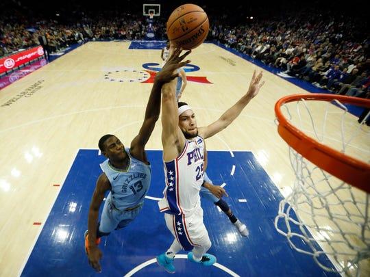 Philadelphia 76ers' Ben Simmons (25) goes up for a dunk past Memphis Grizzlies' Jaren Jackson Jr. (13) during the first half of an NBA basketball game, Sunday, Dec. 2, 2018, in Philadelphia. (AP Photo/Matt Slocum)
